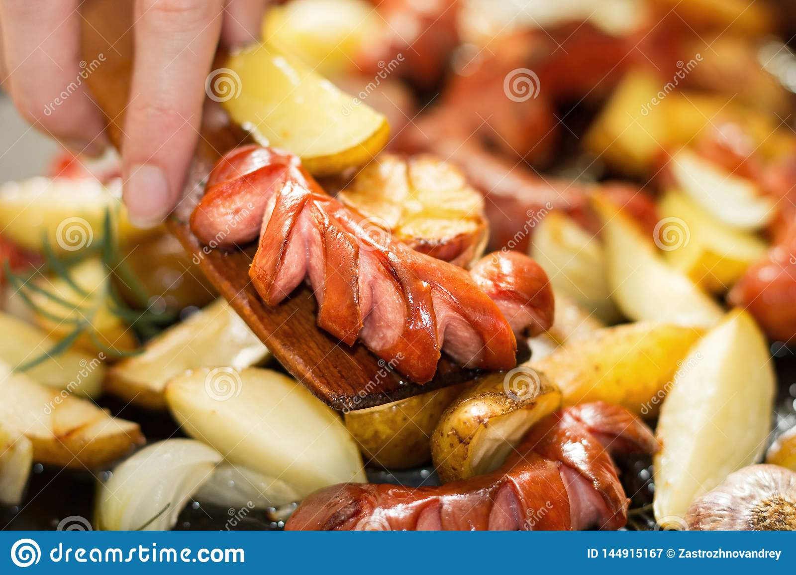 La mano, una esp?tula de madera vierte una cena alta en calor?as y grasa Imagen horizontal