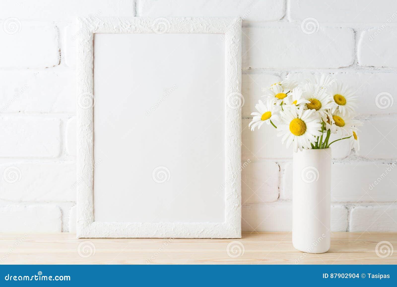 La maquette blanche de cadre avec la fleur de marguerite près a peint le mur de briques