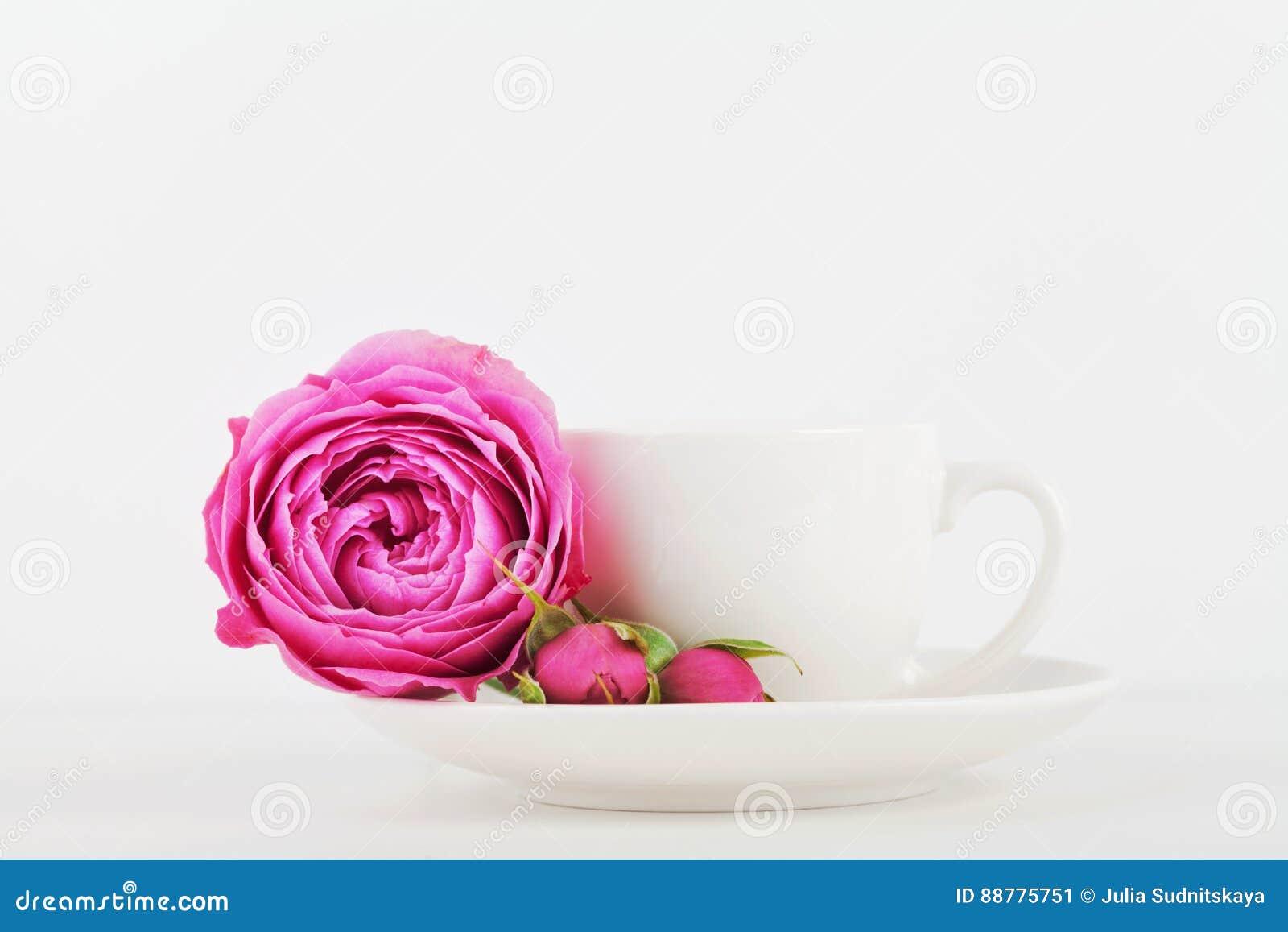 La maquette de la tasse de café et la fleur rose sur le bureau