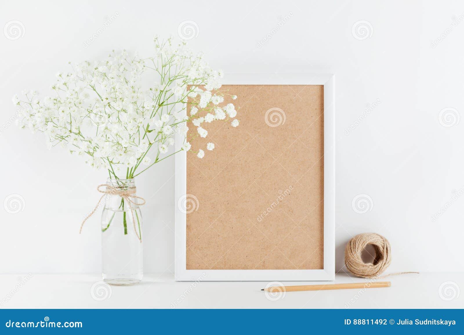La maquette du gypsophila décoré de cadre de tableau fleurit dans le vase sur la table de fonctionnement blanche avec l espace pr