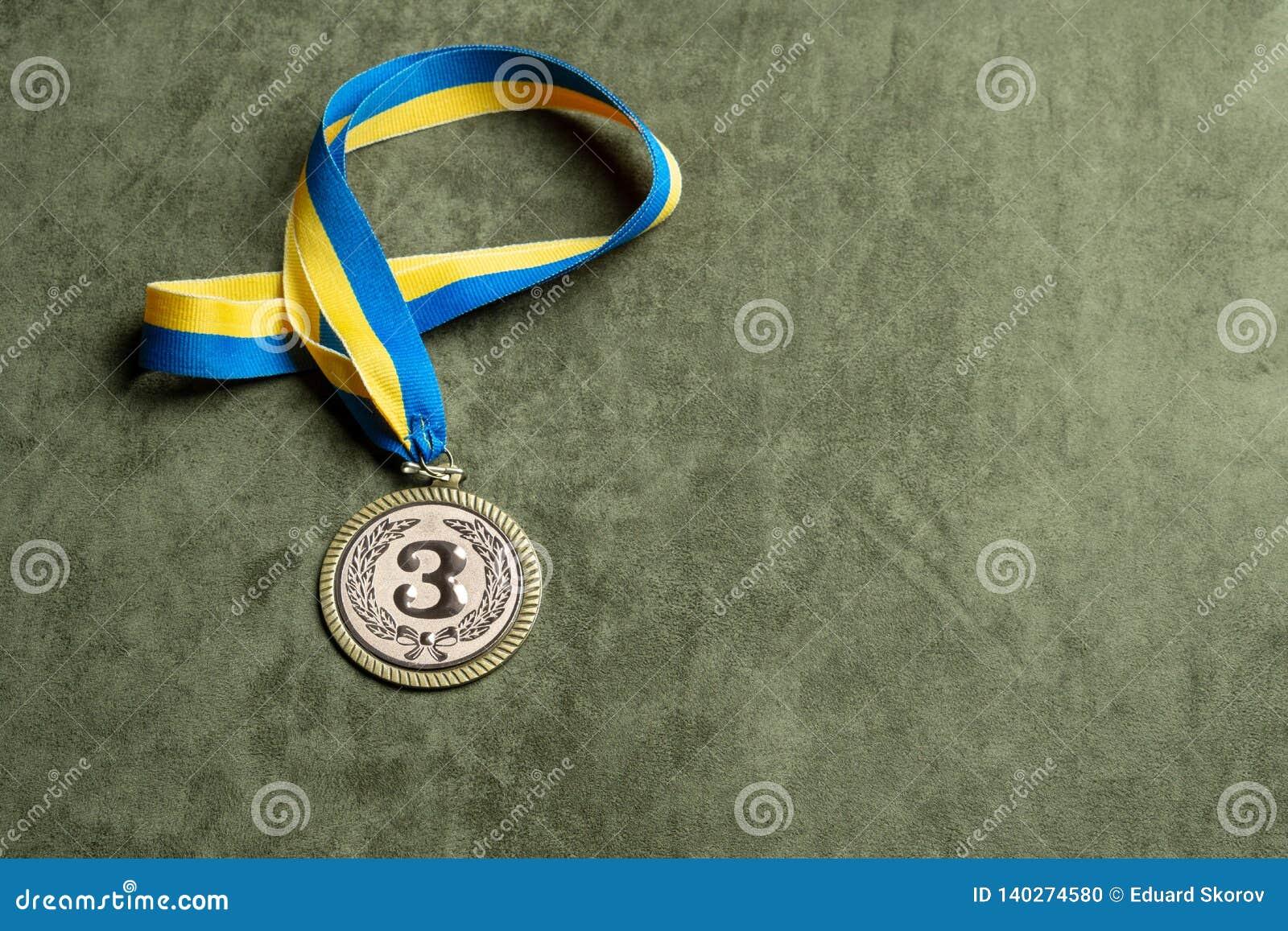 La medalla de bronce para el tercer lugar con la cinta amarillo-azul, copia-espacio