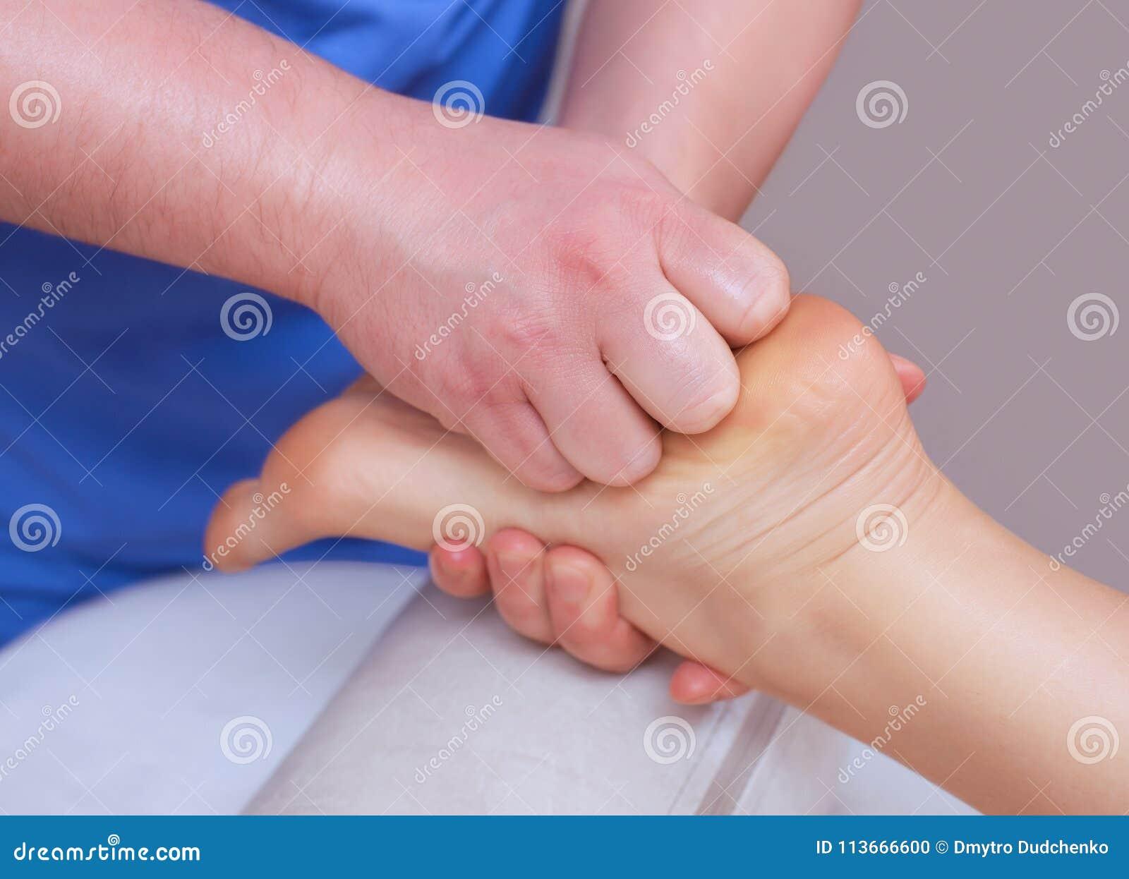 La medico-podologia fa un esame e un massaggio del piede paziente del ` s