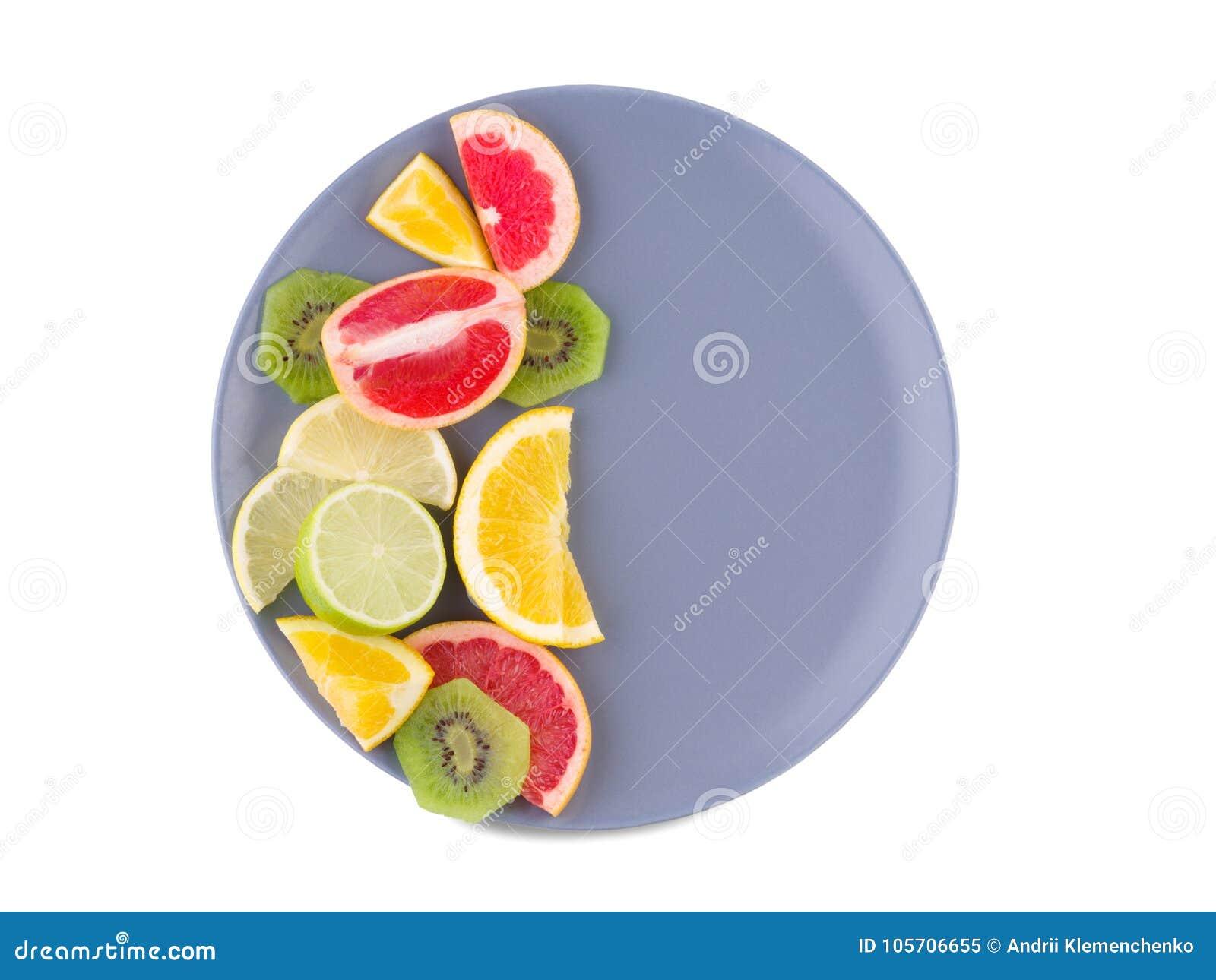 La metà del piatto è piena dei frutti tropicali su un fondo isolato bianco Vista da sopra