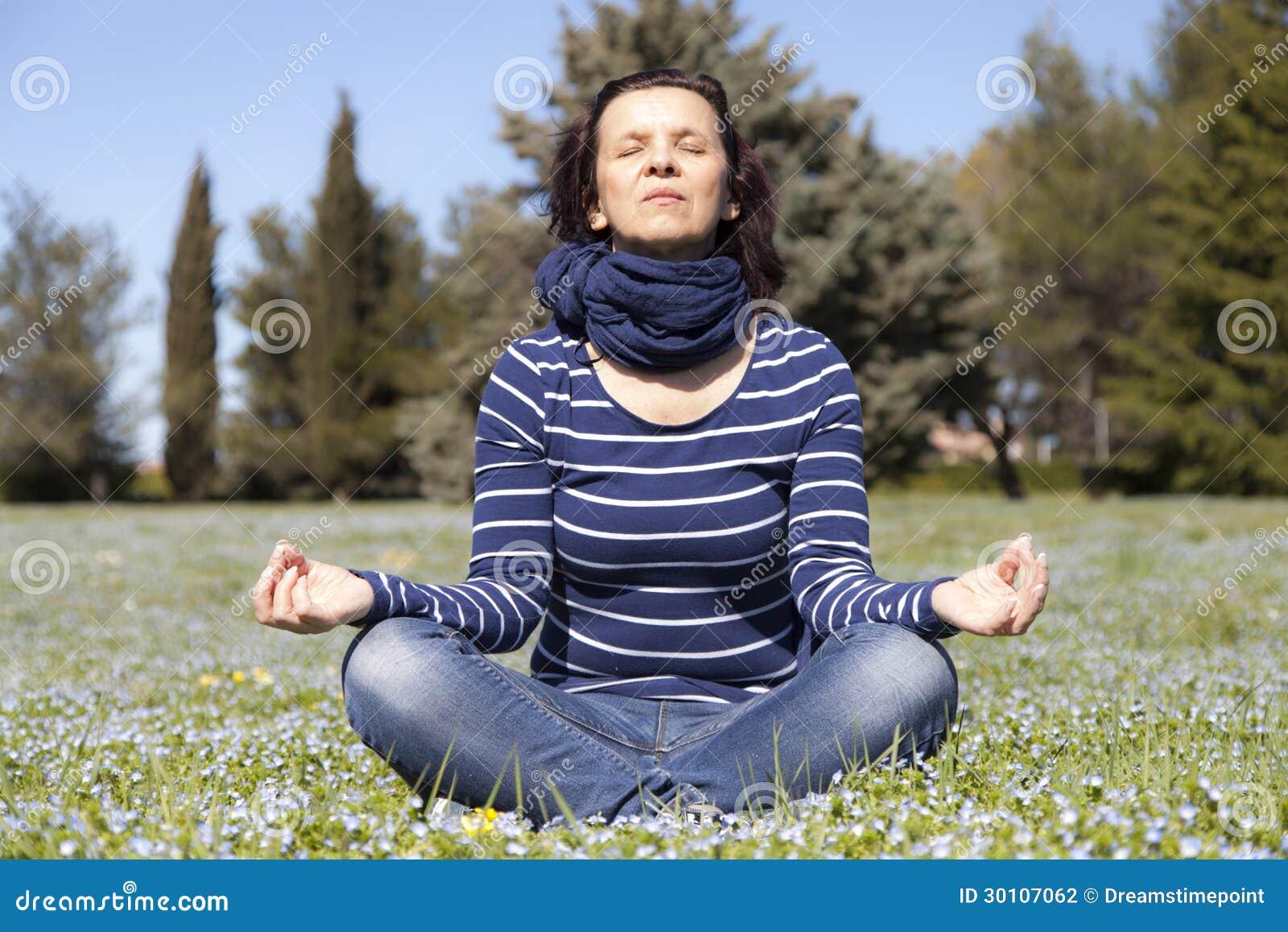 La mi femme âgée faisant le yoga s exerce dehors