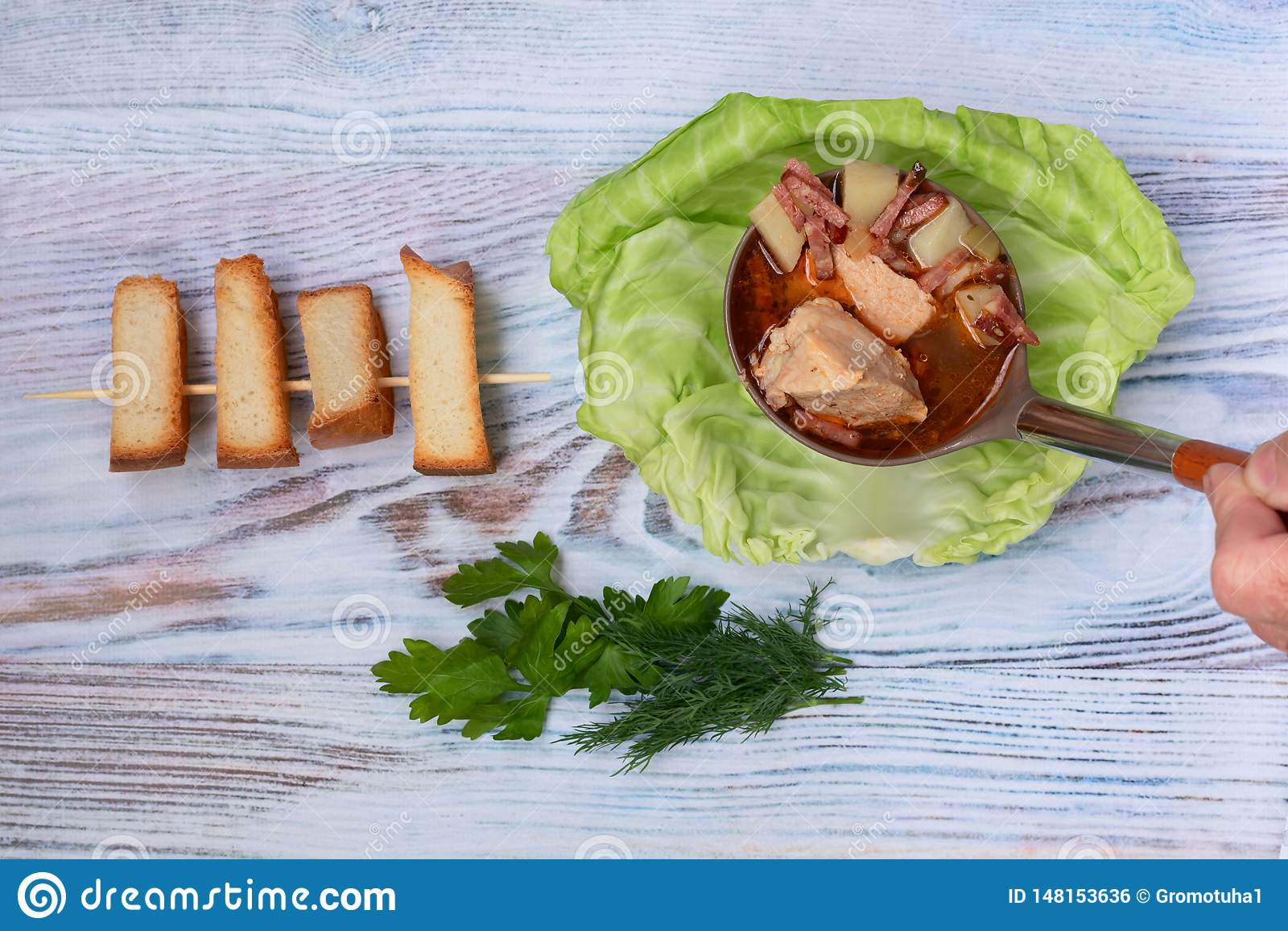 La minestra cucinata in brodo della carne con le erbe ed i crostini freschi è versata in un piatto con la foglia del cavolo