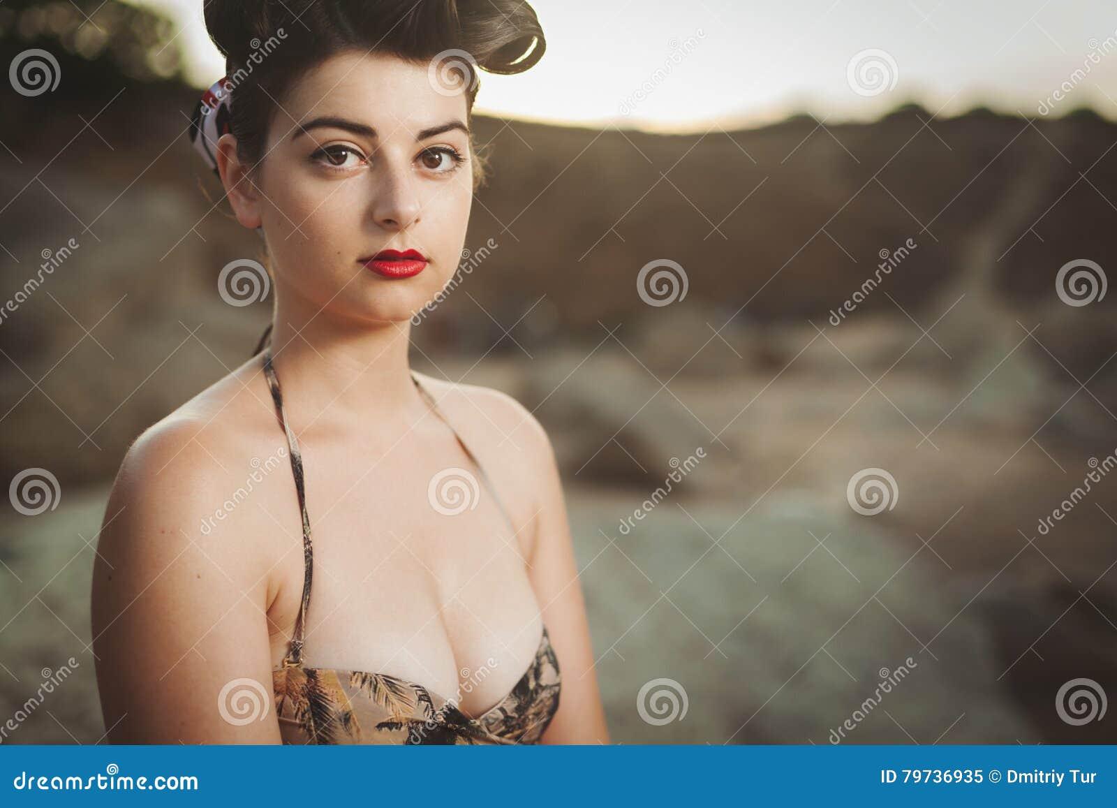 La mirada modela vistió a la muchacha que se sentaba en las rocas