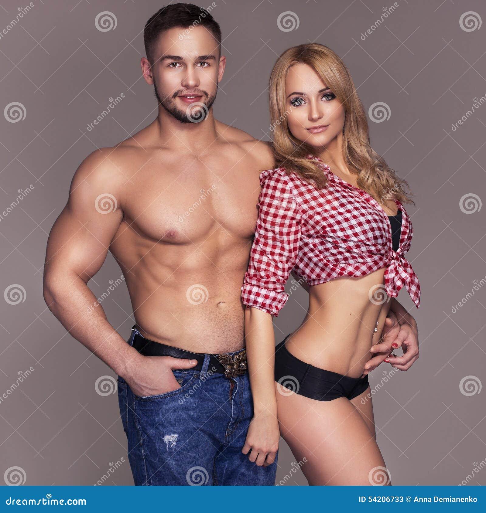 La misura sexy muscled le coppie in jeans e pantaloni e maglietta del plaid sopra