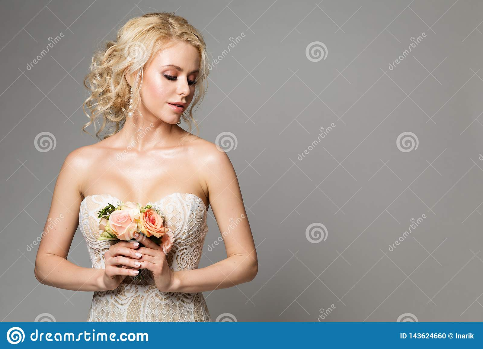 La moda modela el retrato con el ramo de la flor, el maquillaje hermoso y el peinado, tiro de la novia de la mujer del estudio de