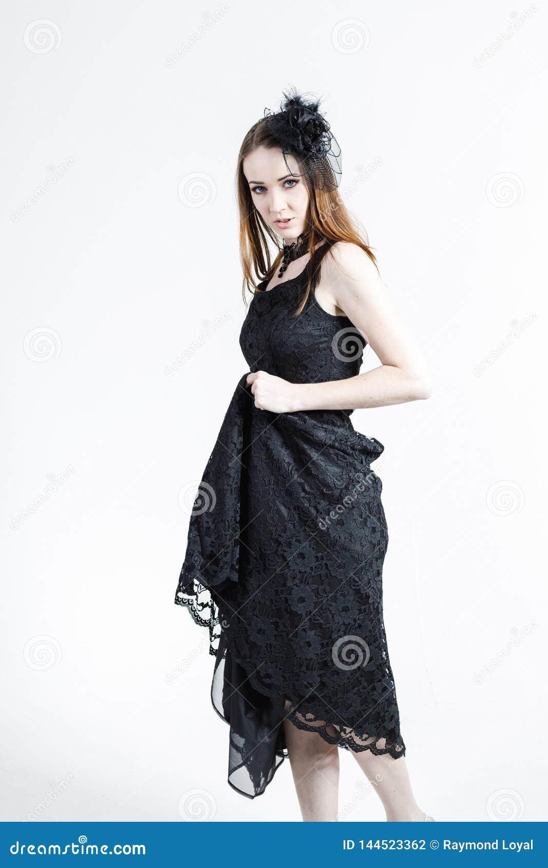 La moda tiró de una mujer joven en un vestido con el sombrero