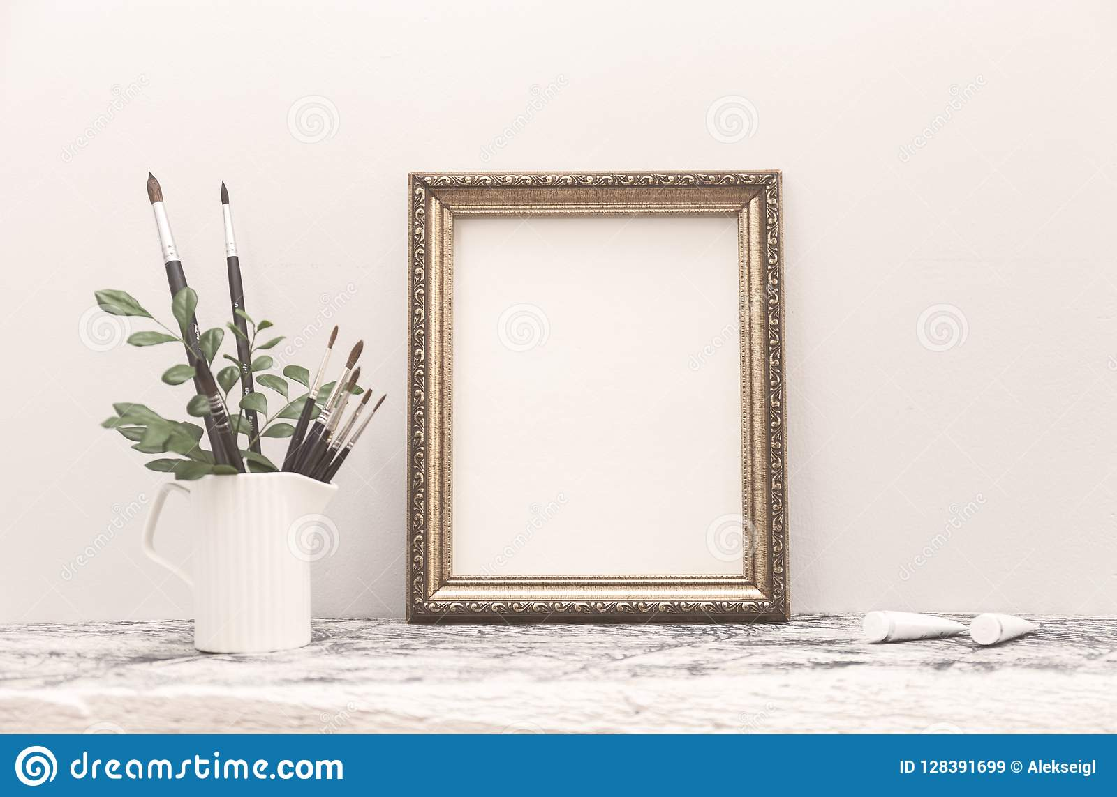 La mofa de oro del marco para arriba en la tabla y los cepillos blancos del arte