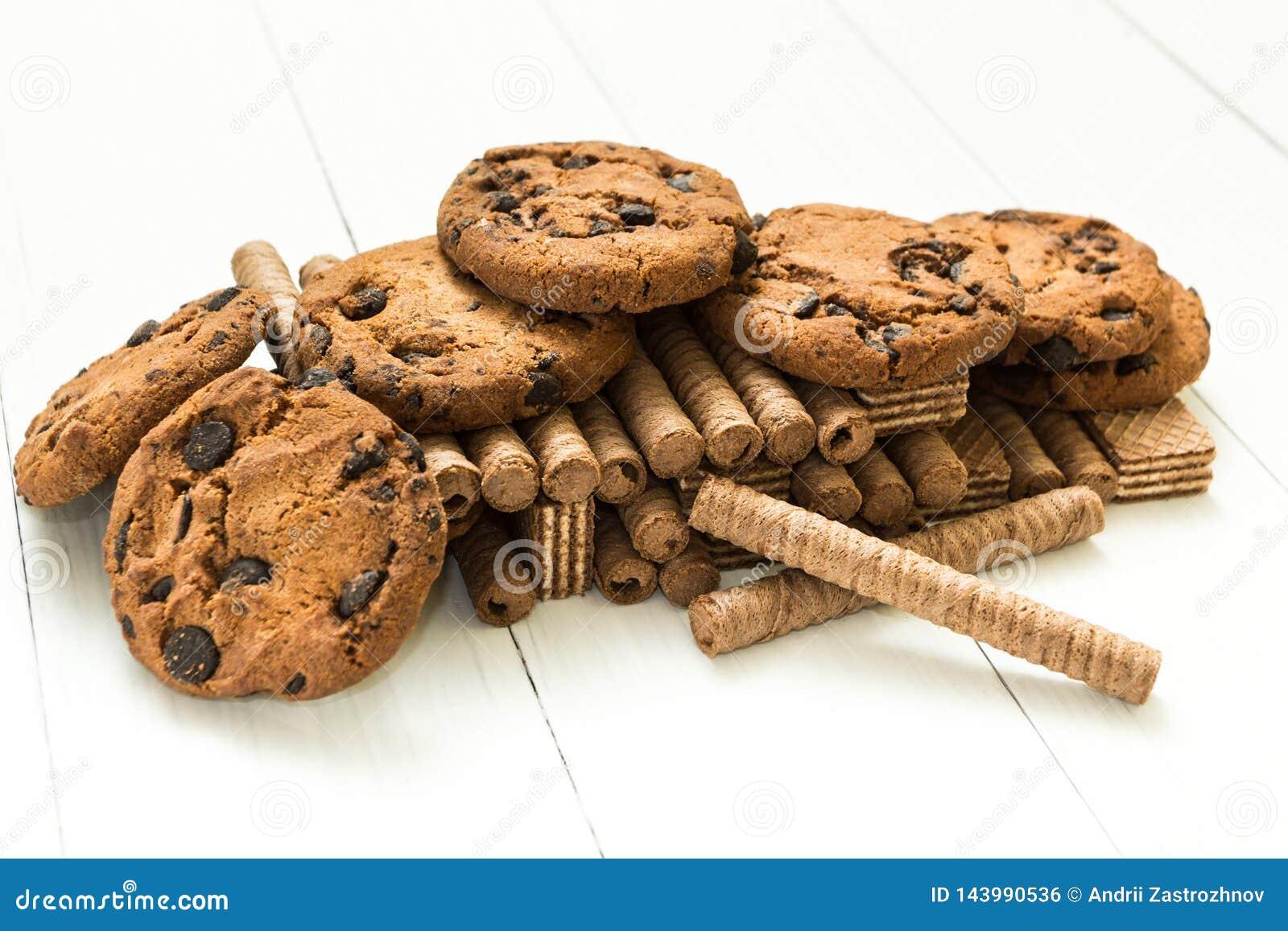 La monta?a mezcl? los rollos de la galleta del chocolate, las galletas y la galleta cl?sica en una tabla blanca de madera Dulce-t