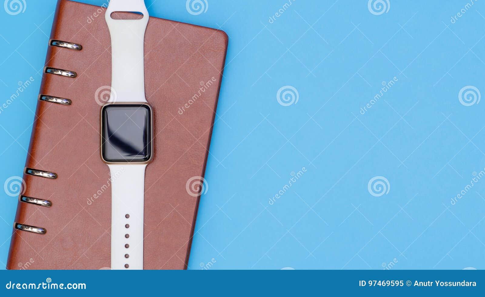 La montre intelligente sur le carnet pour organisent le concept sur le bleu