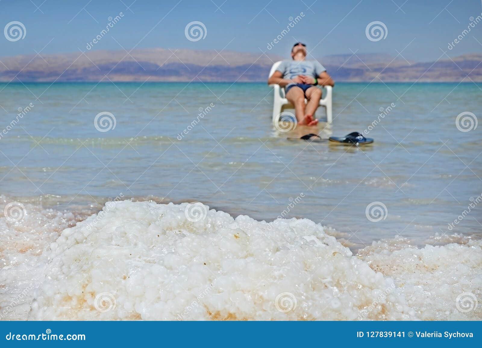 La morena joven del individuo toma el sol en una silla en el mar muerto Opinión Jordan Mountains de las orillas del mar muerto en