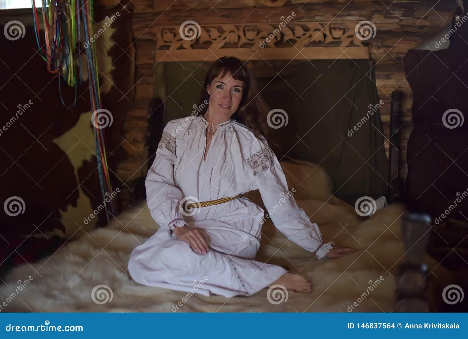 La morenita en la camisa pasada de moda de lino blanca con bordado se sienta en una cama medieval