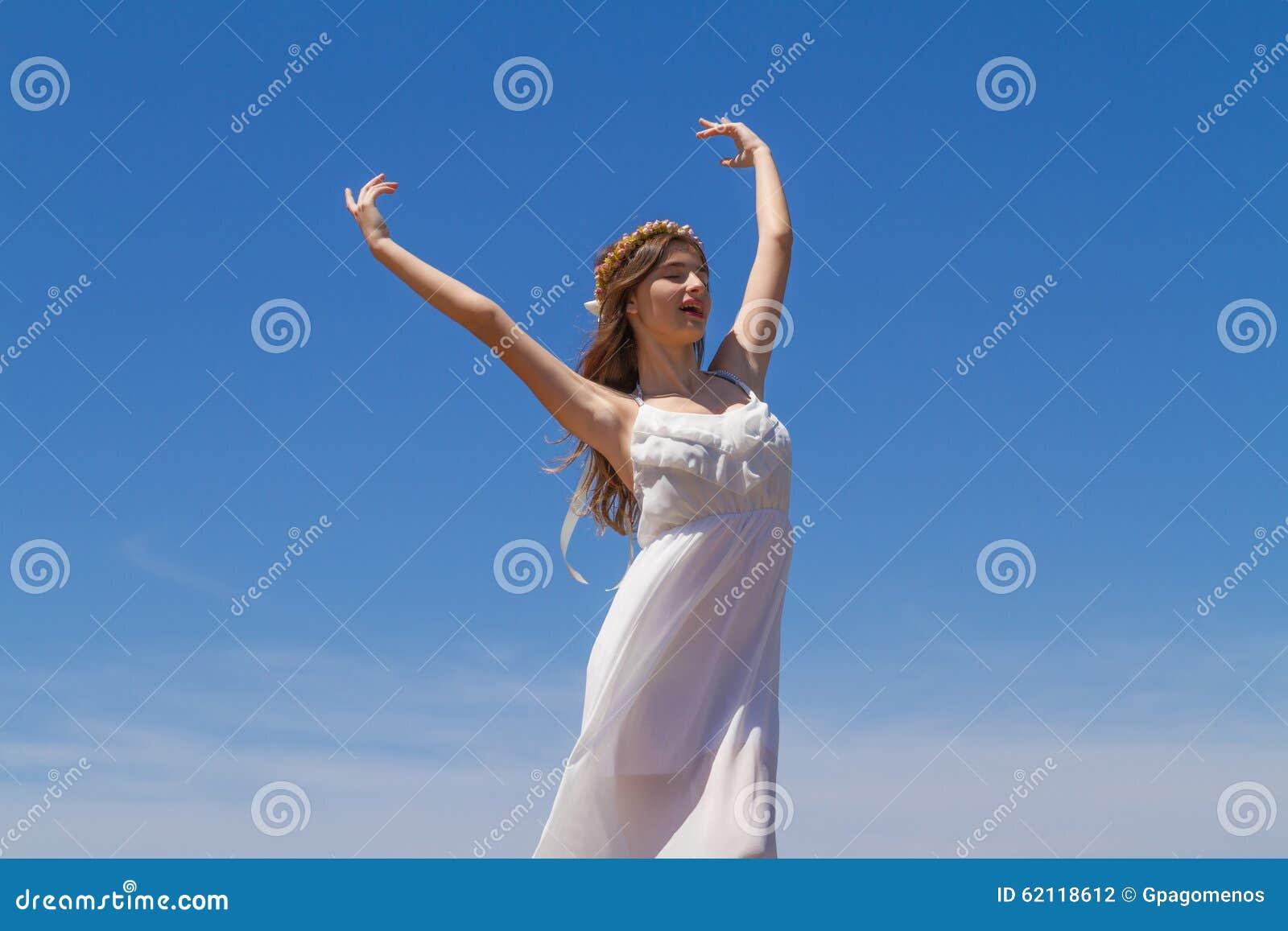 La morenita joven en el vestido débil blanco goza de