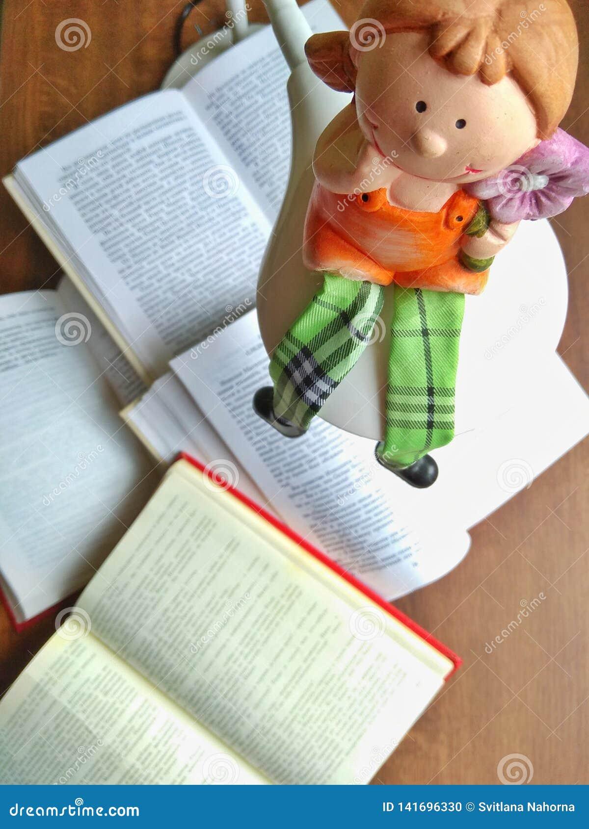 La muñeca de la arcilla se sienta en la lámpara Muchos libros abiertos en una tabla de madera