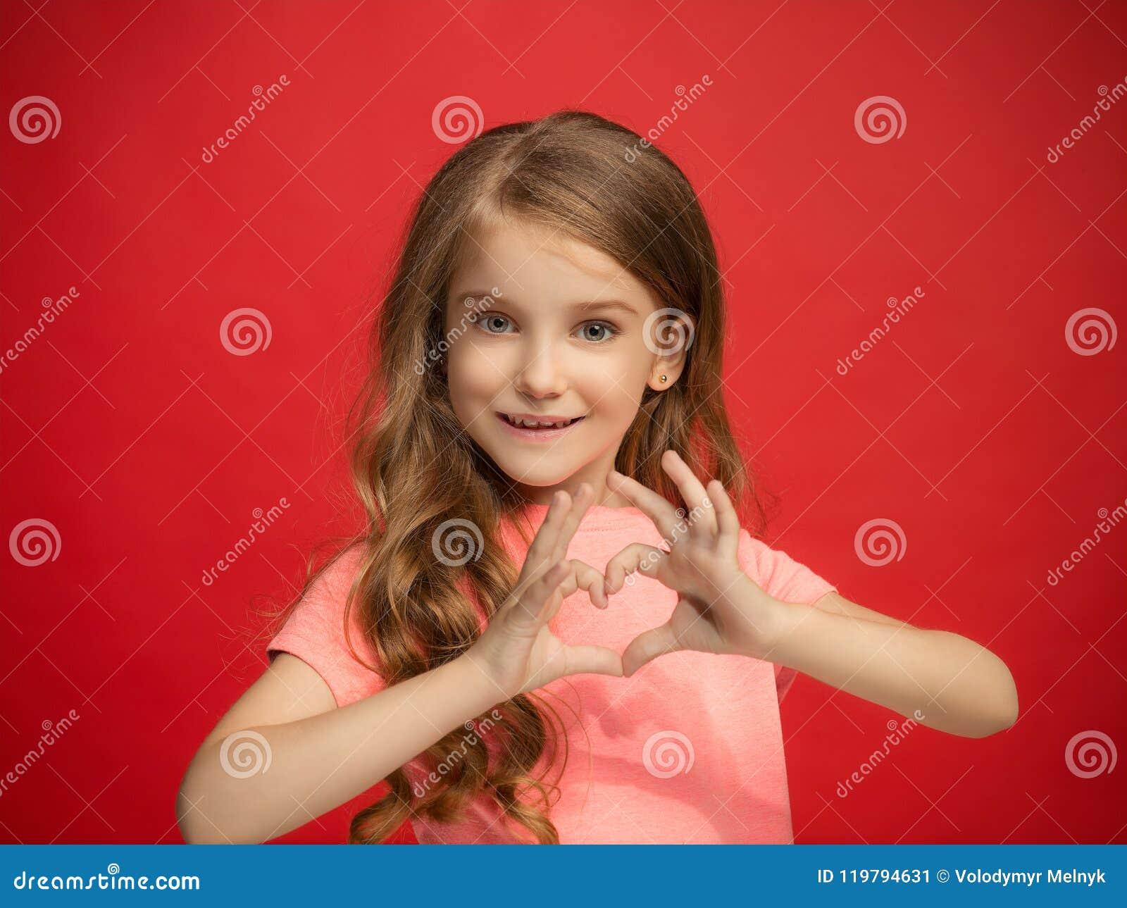 La muchacha adolescente feliz que se opone y que sonríe contra fondo rojo