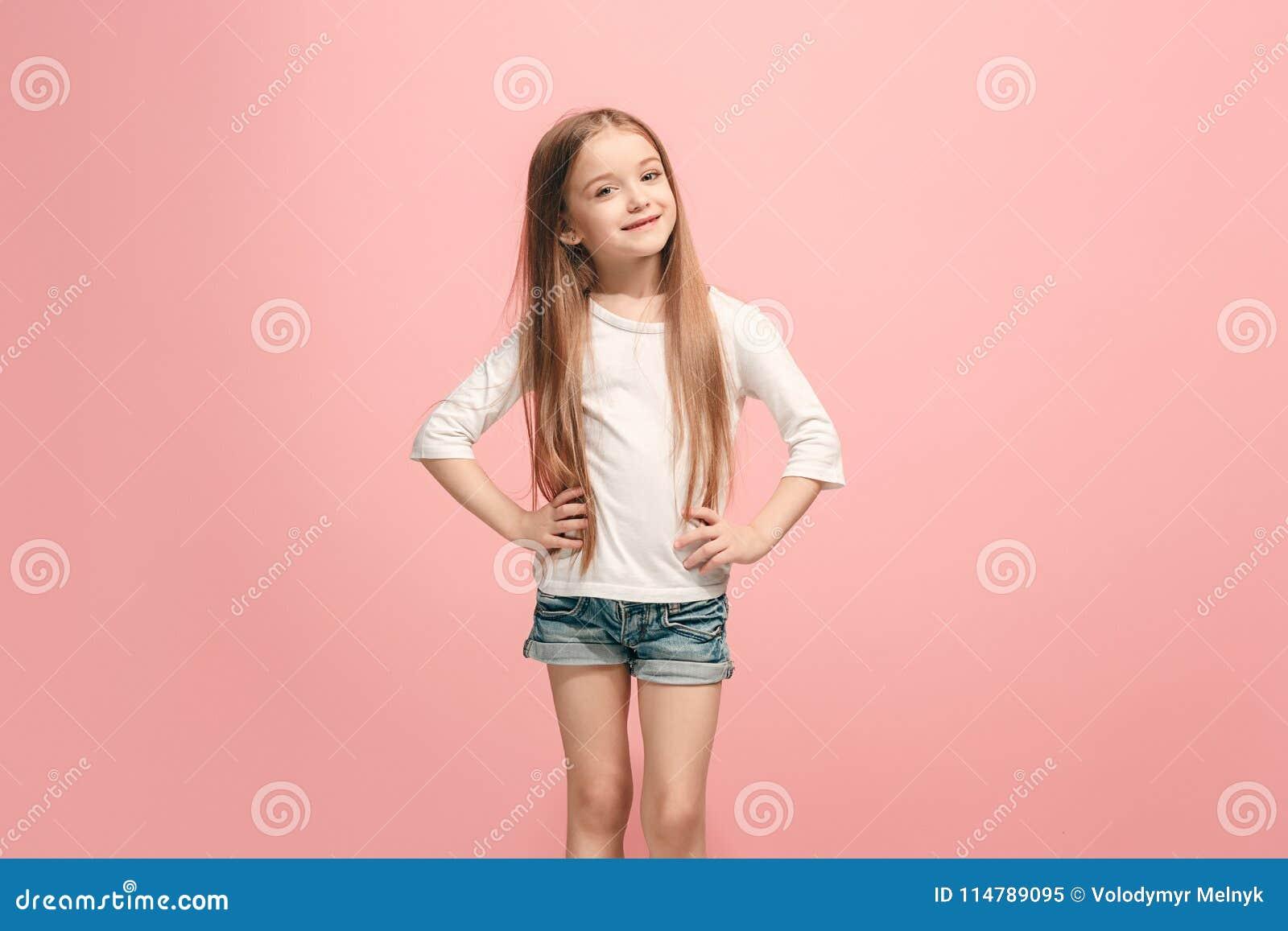 La muchacha adolescente feliz que se opone y que sonríe contra fondo rosado
