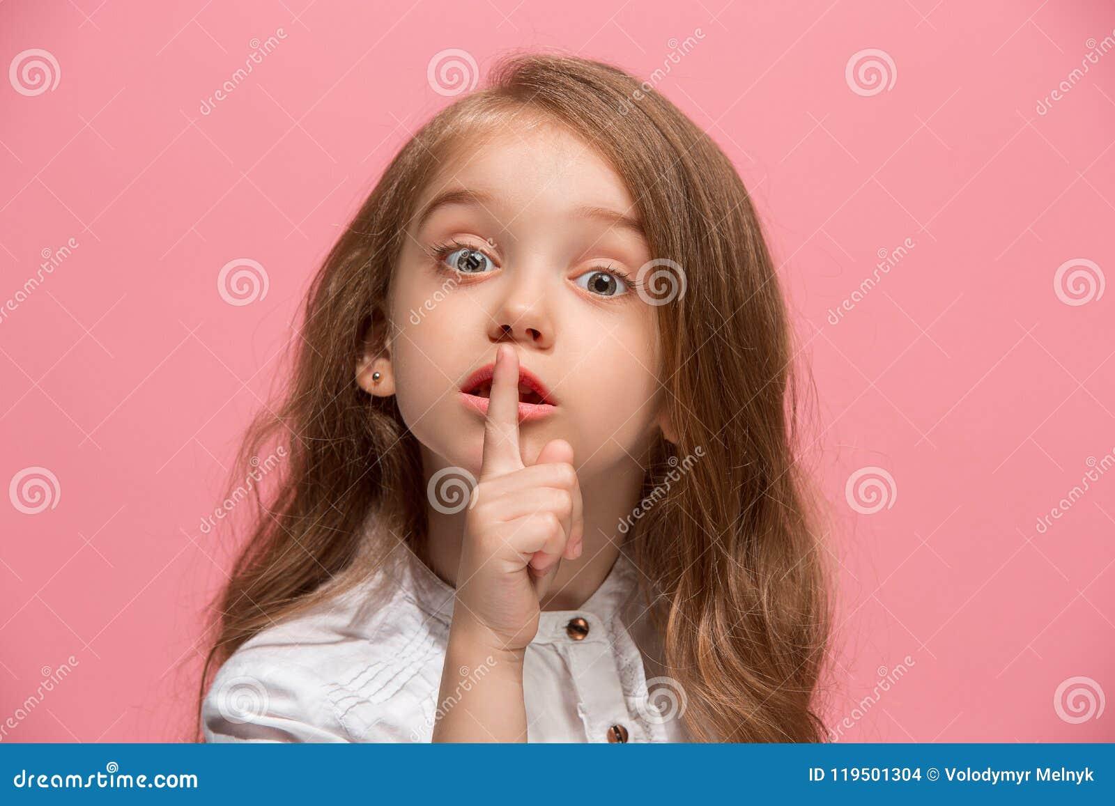 La muchacha adolescente joven que susurra un secreto detrás de ella entrega el fondo rosado