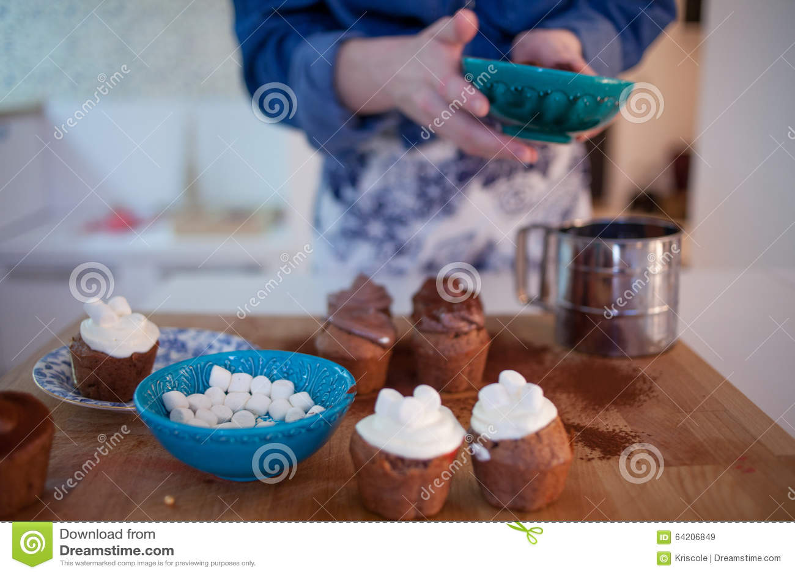 La muchacha adorna las magdalenas, sosteniendo la placa, los molletes
