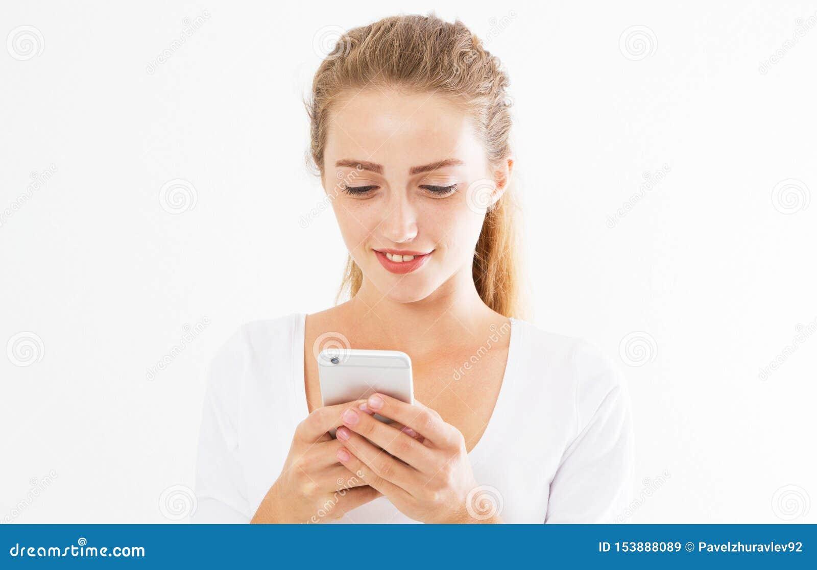 La muchacha alegre encantadora est? leyendo el mensaje de texto agradable en el tel?fono m?vil de su novio durante su tiempo de r