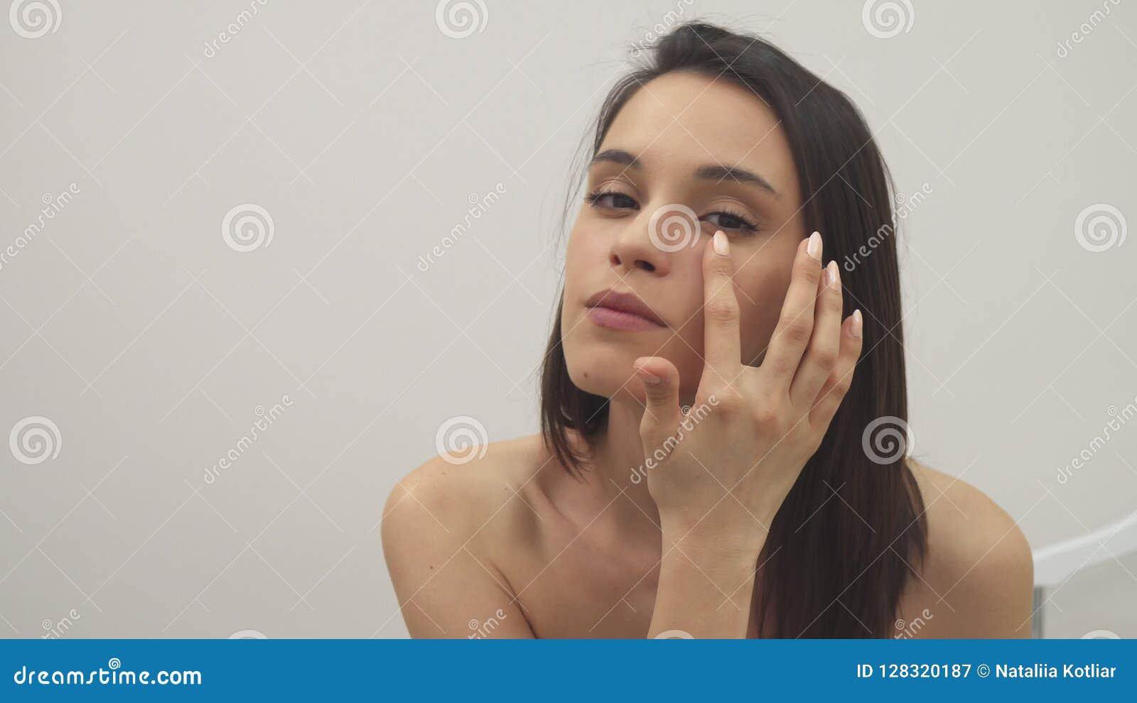 La muchacha aplica el tratamiento facial