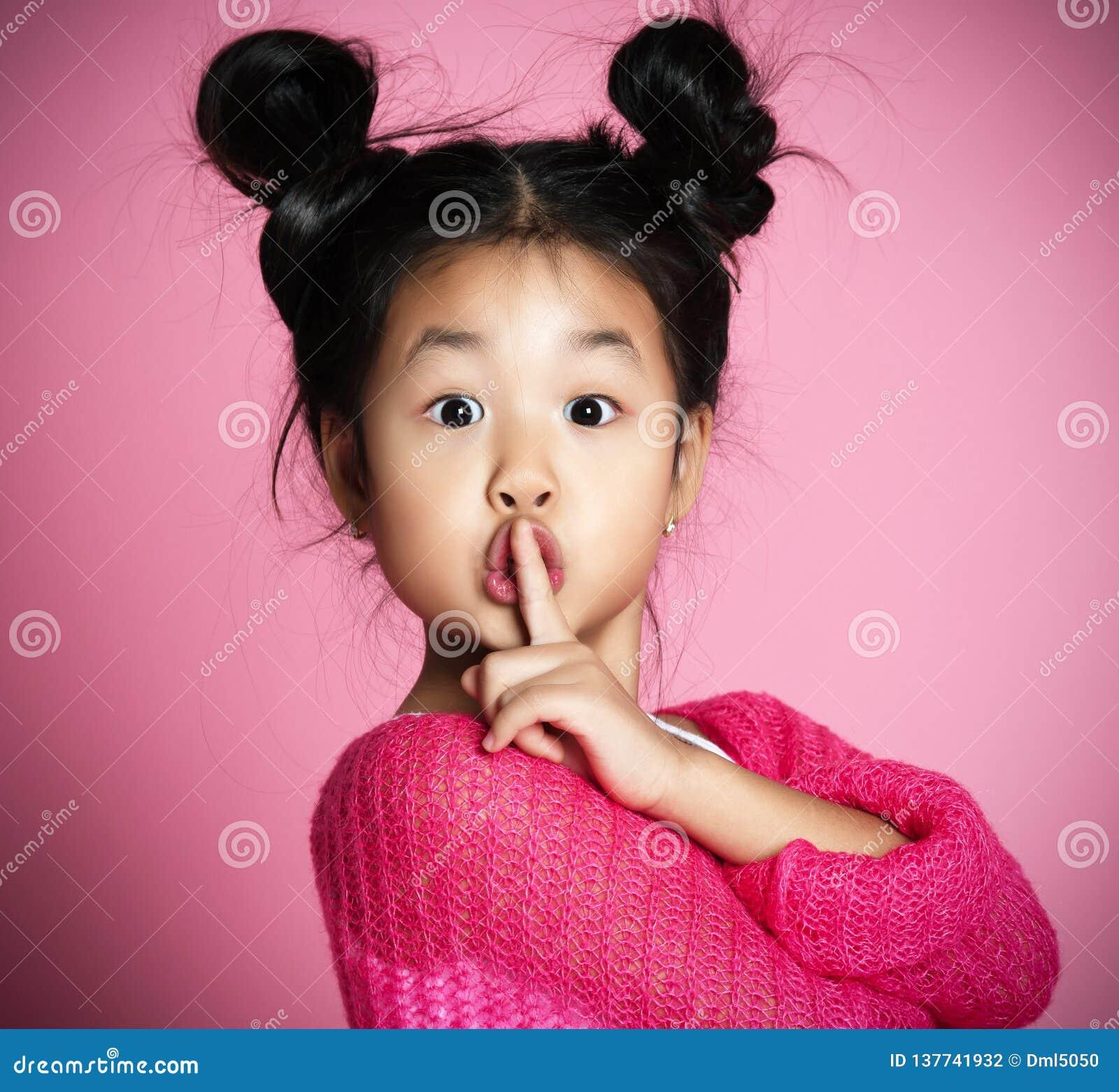 La muchacha asiática del niño en suéter rosado muestra shh cierre de la muestra encima del retrato