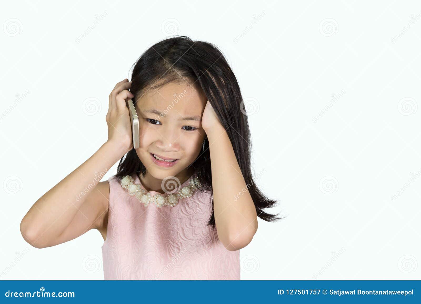 La muchacha asiática está utilizando un teléfono móvil aislado en el fondo blanco, tensión, triste