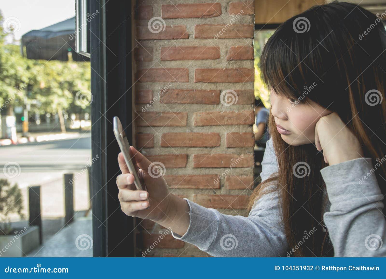 La muchacha asiática hermosa utilizó el teléfono en la cafetería, finanzas del negocio