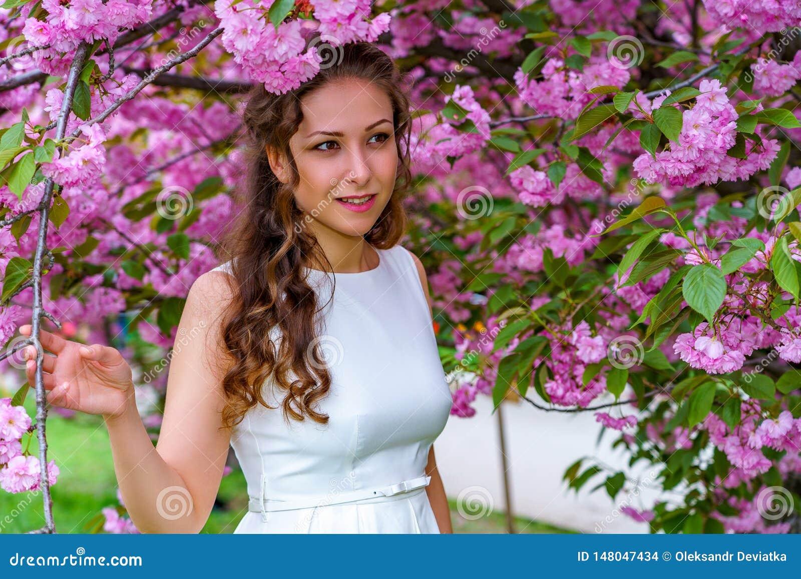 La muchacha atractiva con el pelo rizado en el vestido blanco está caminando en el jardín de Sakura del flor entre las flores ros