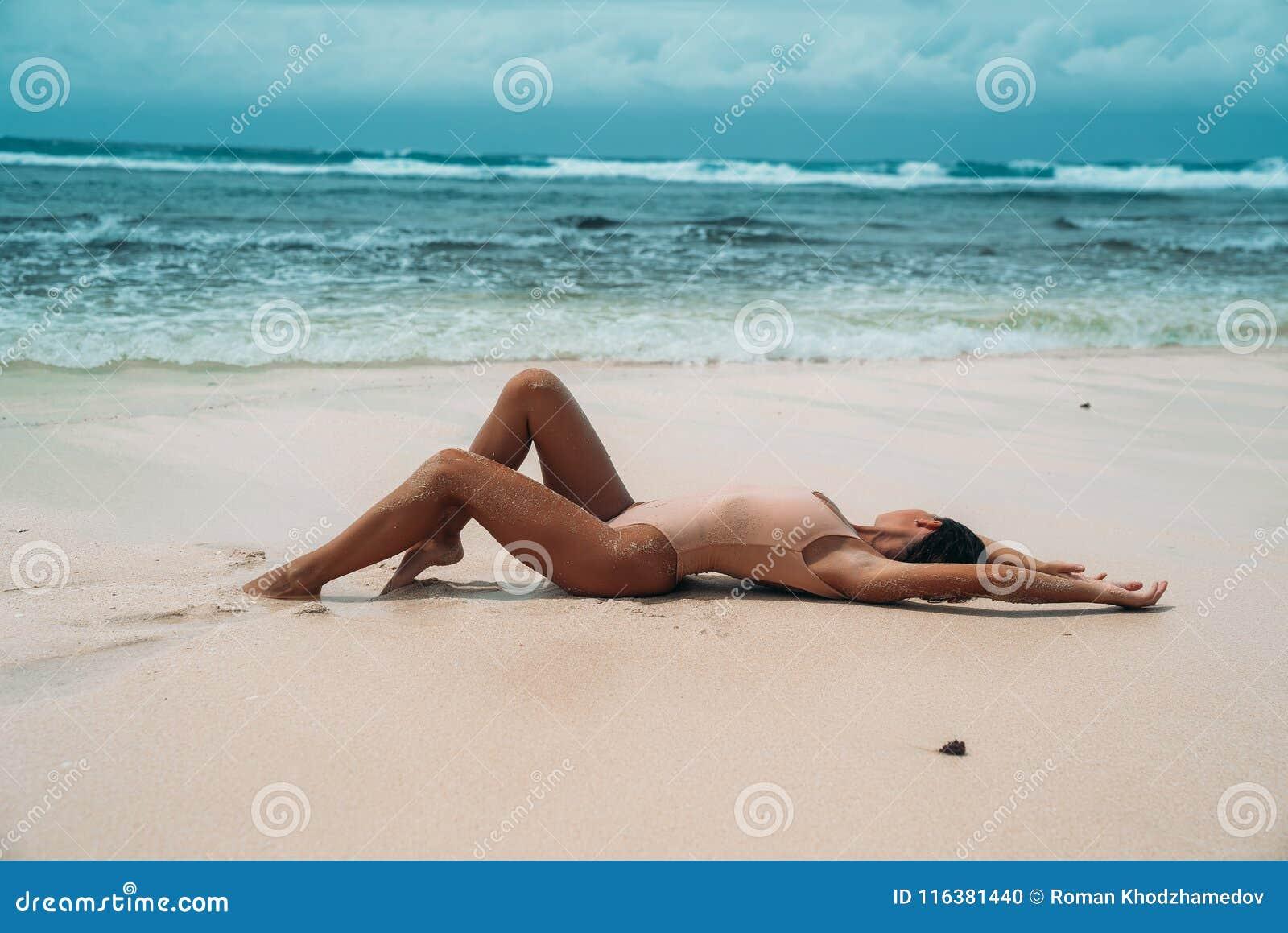 La muchacha atractiva con los deportes figura mentiras en la arena blanca cerca del océano Una mujer joven goza el relajarse en l