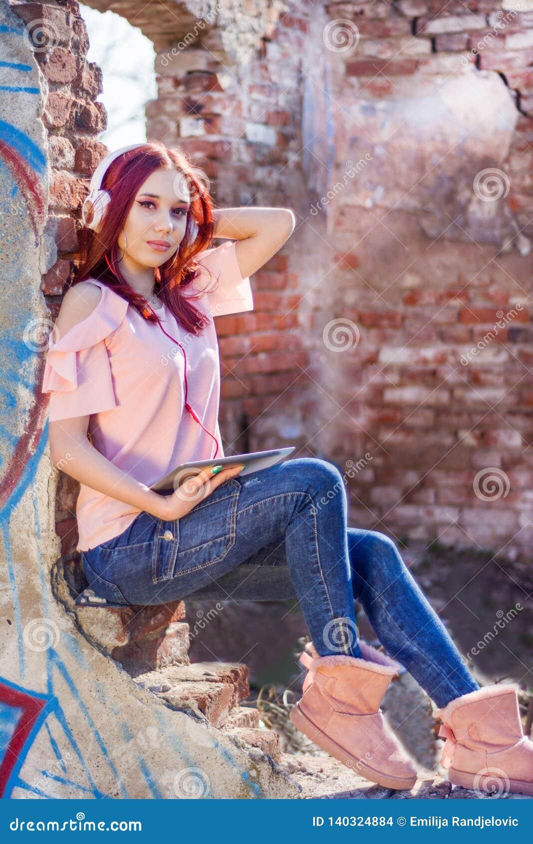 La muchacha atractiva de los pelirrojos con la tableta digital que escucha la música en los auriculares en ruinas empareda ladril