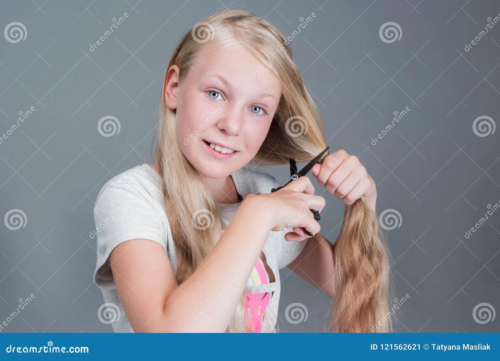 La muchacha atractiva del chaild está cortando su pelo natural rubio largo