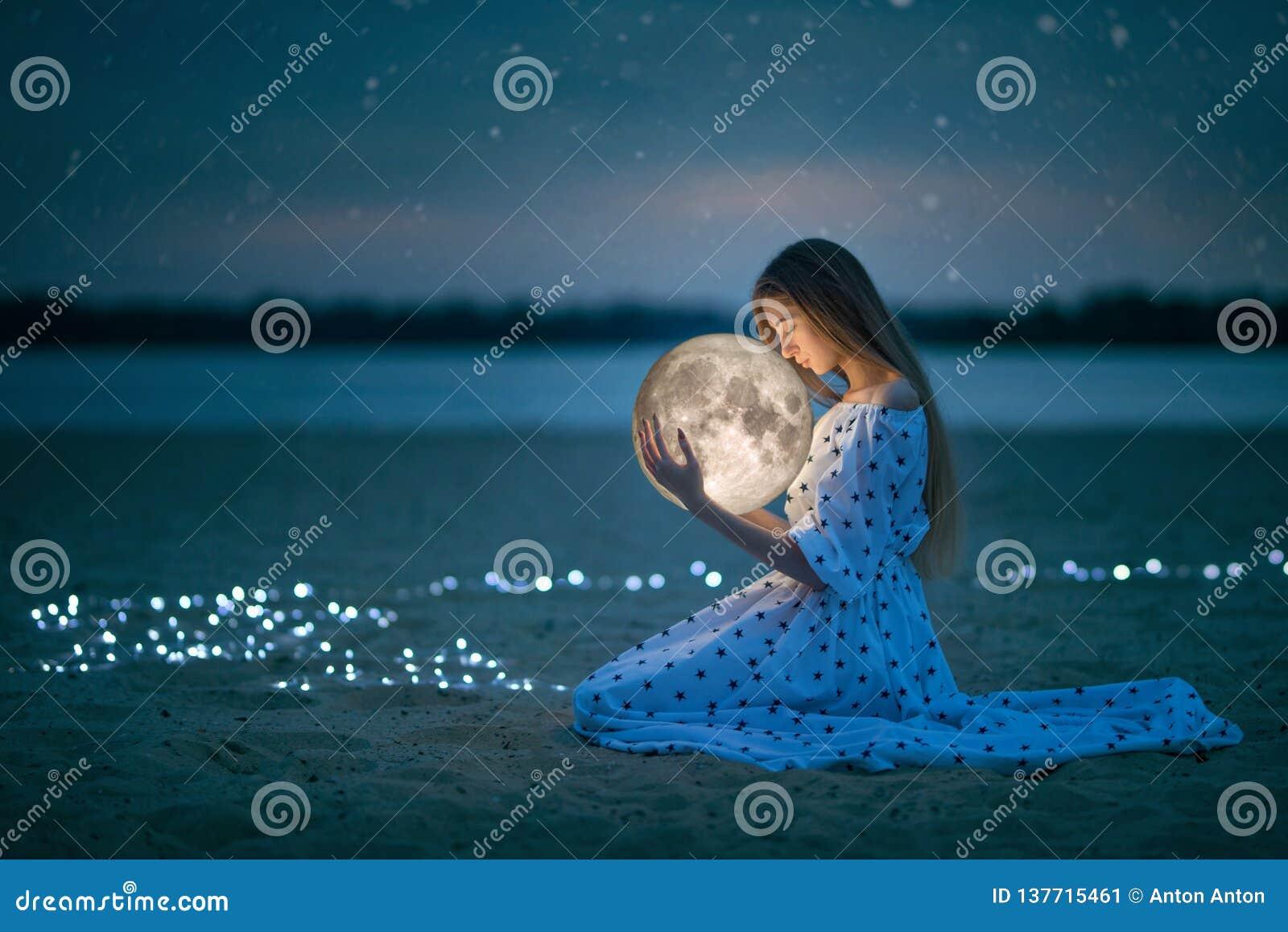 La muchacha atractiva hermosa en una playa de la noche con la arena y las estrellas abraza la luna, fotografía artística