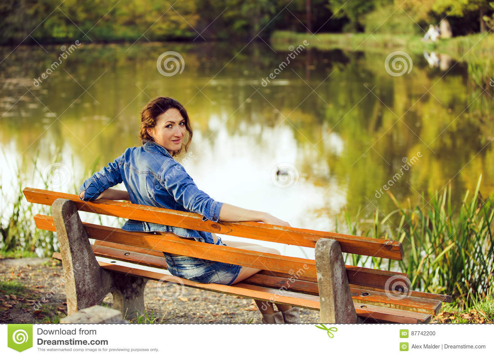 La muchacha atractiva que se sienta en un banco