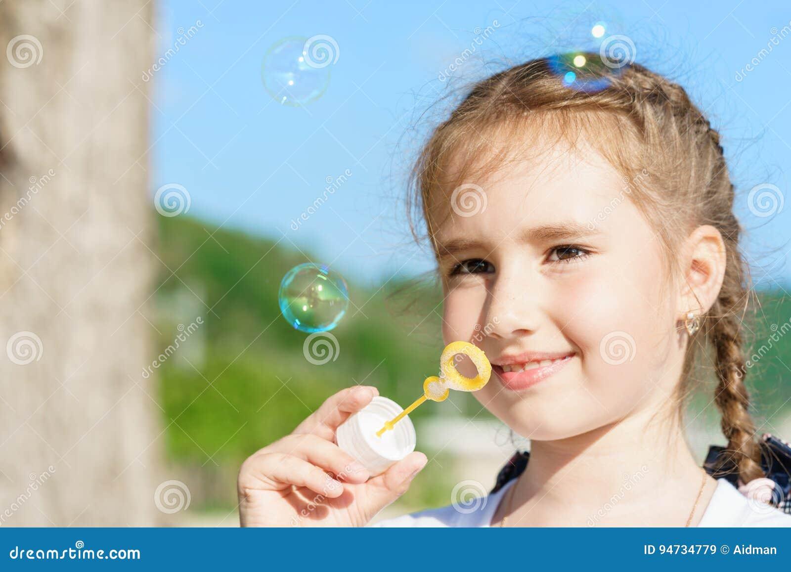 La muchacha bastante europea del niño de los jóvenes con sonrisa linda está soplando burbujas en cielo azul inferior al aire libr