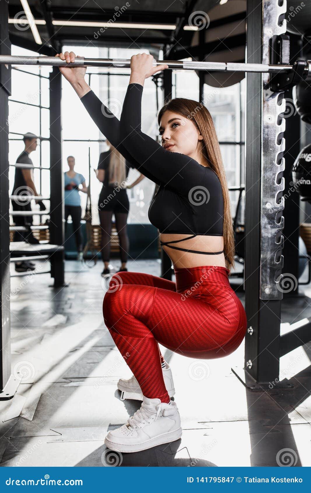 La muchacha bonita atlética en ropa brillante elegante de los deportes presenta al lado de la barra horizontal en el gimnasio mod