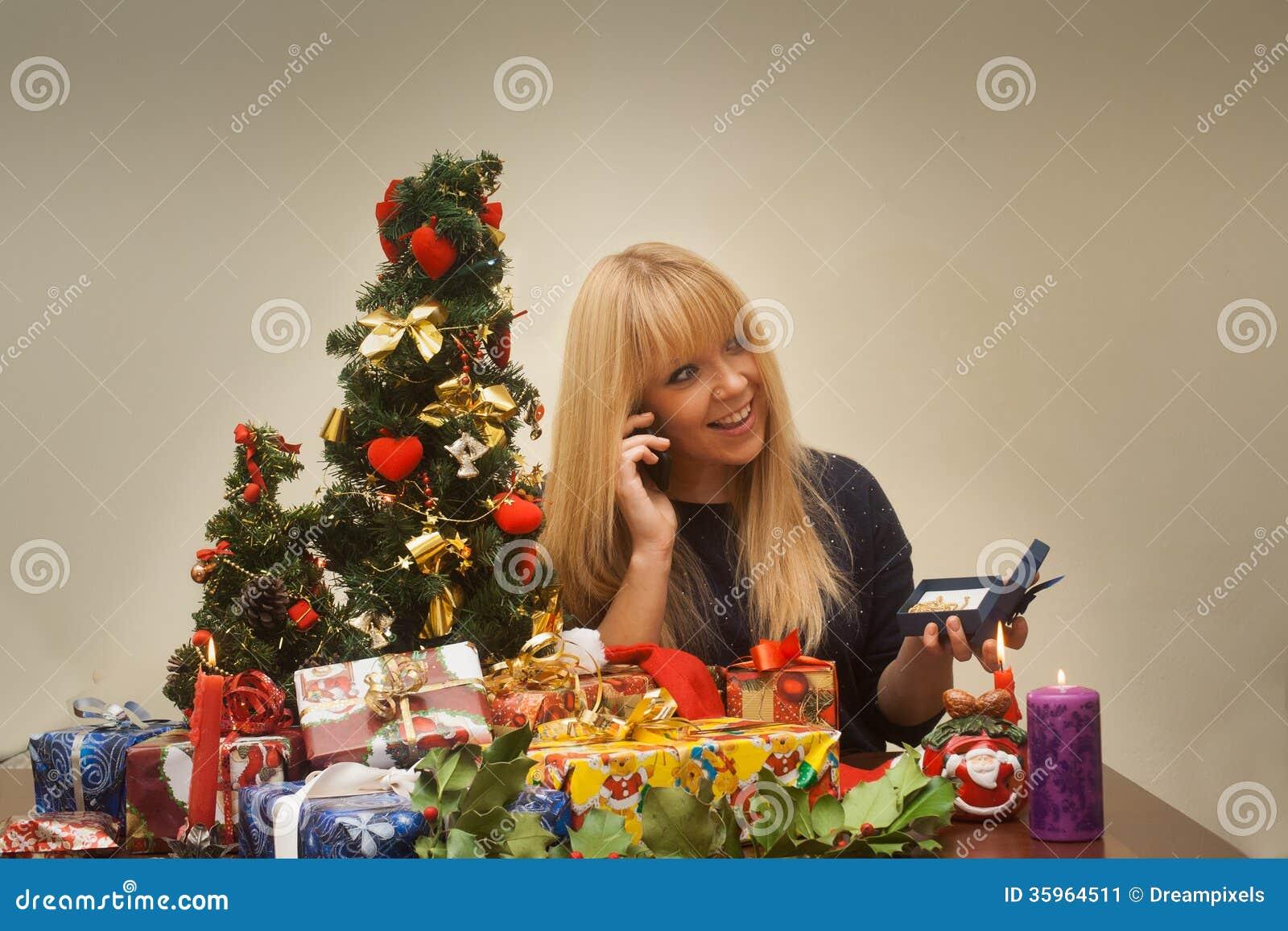La muchacha bonita consigue jewellry para el regalo de la Navidad y sonríe