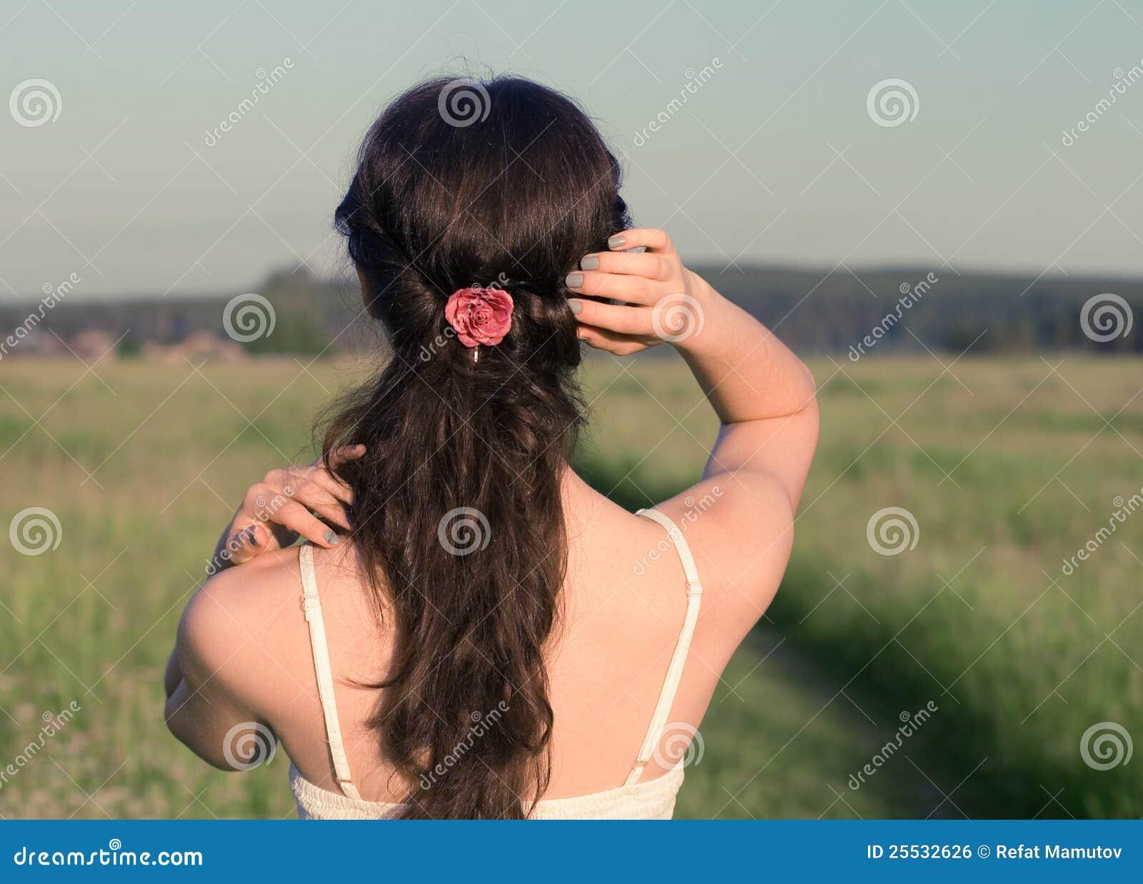 La muchacha bonita está recorriendo en un campo.