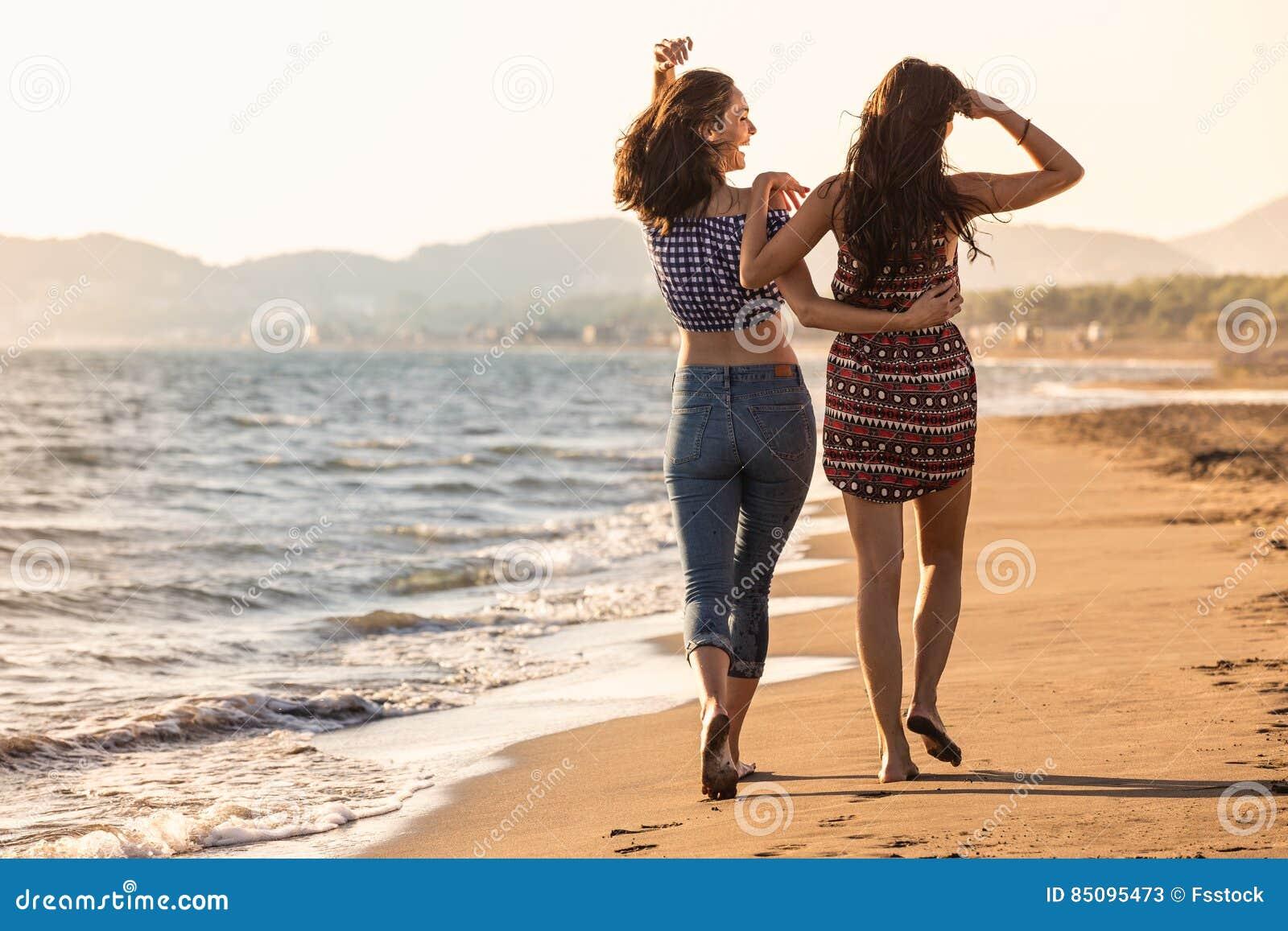 La muchacha bonita se divierte con su novia en la playa