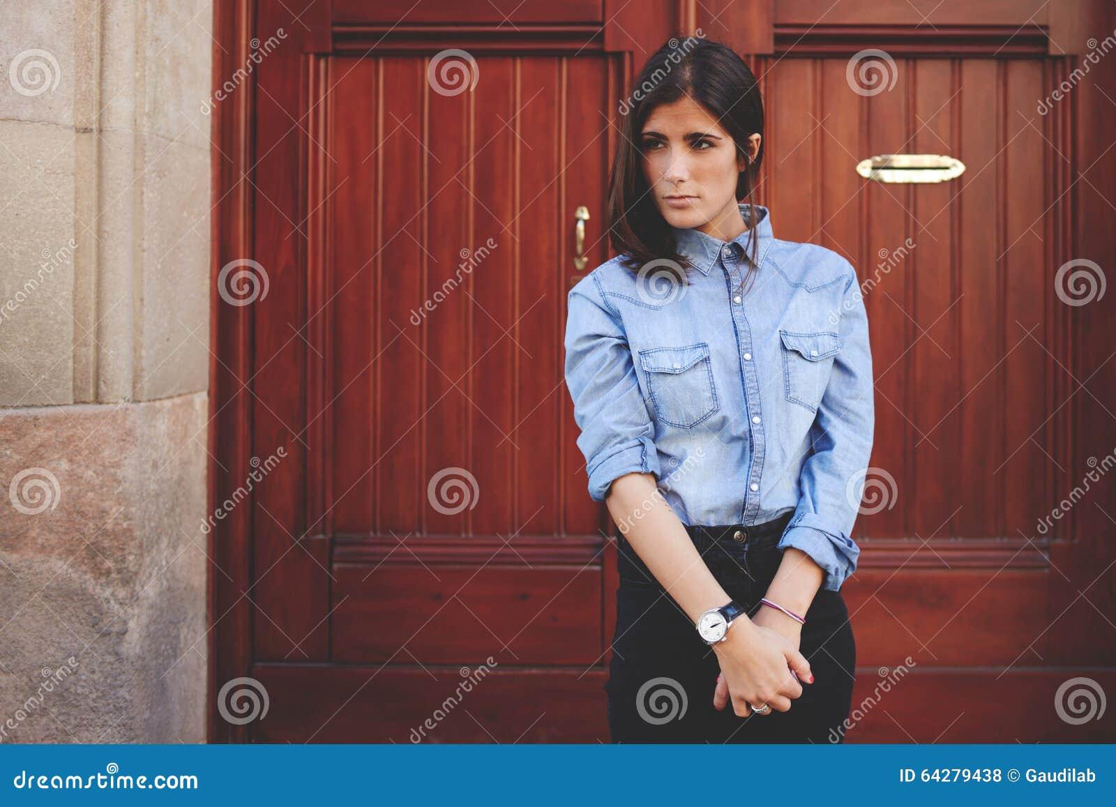La muchacha bonita se está colocando delante de la puerta de madera, señora magnífica que presenta a un fotógrafo Sesión de foto