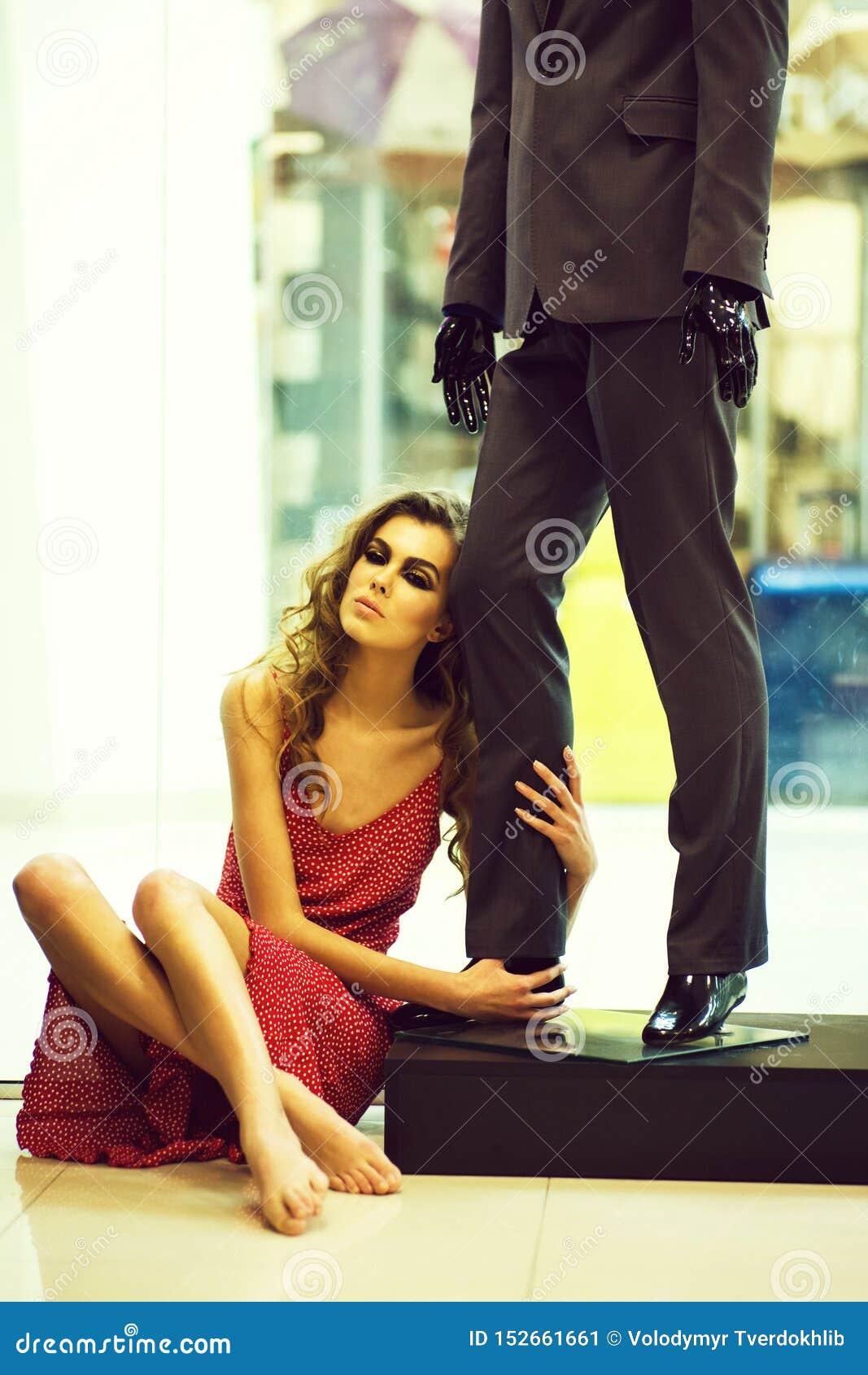 La muchacha bonita se sienta en piso en el maniqu? masculino en tienda