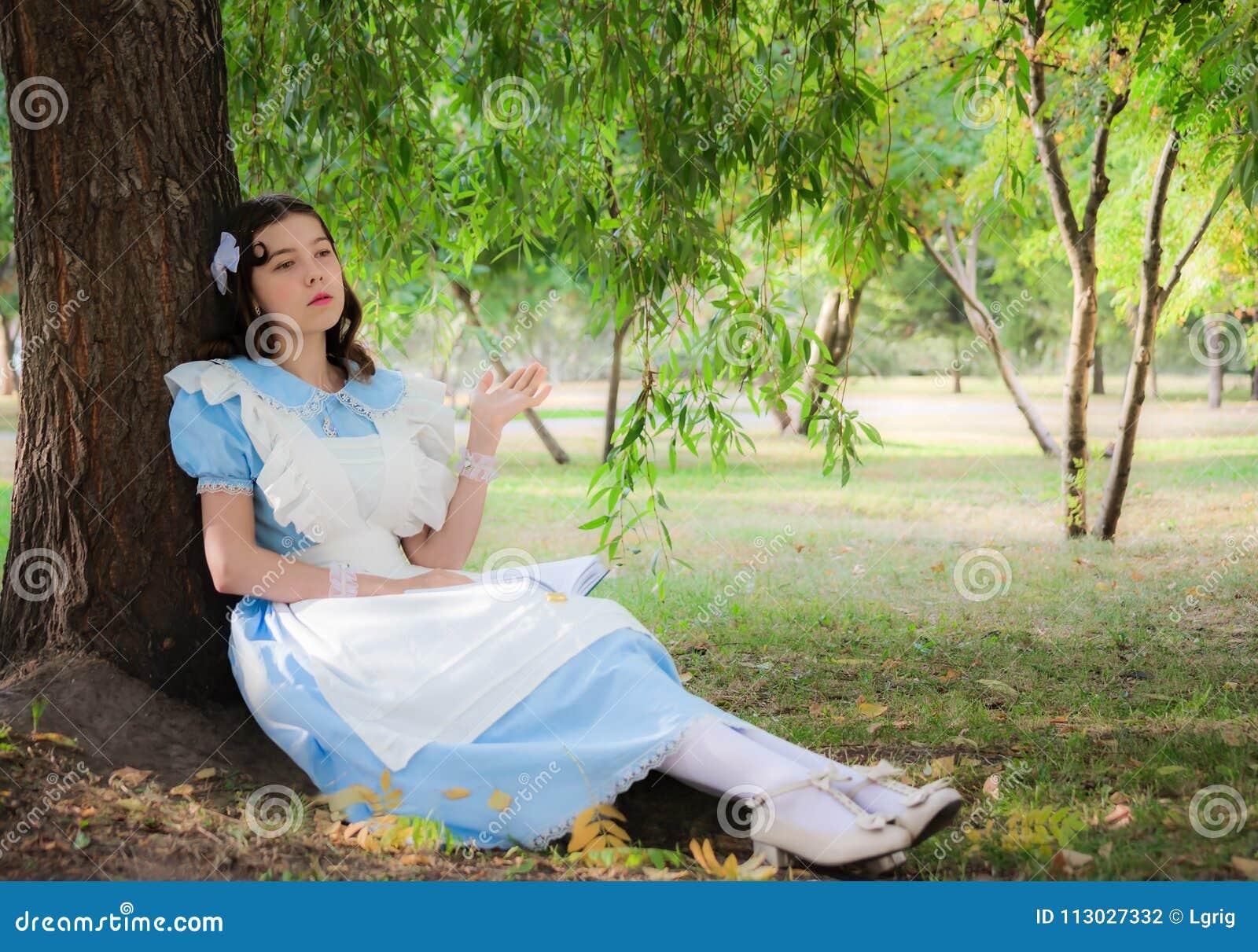 La muchacha cansó del libro aburrido de la lectura que se sentaba debajo de un árbol