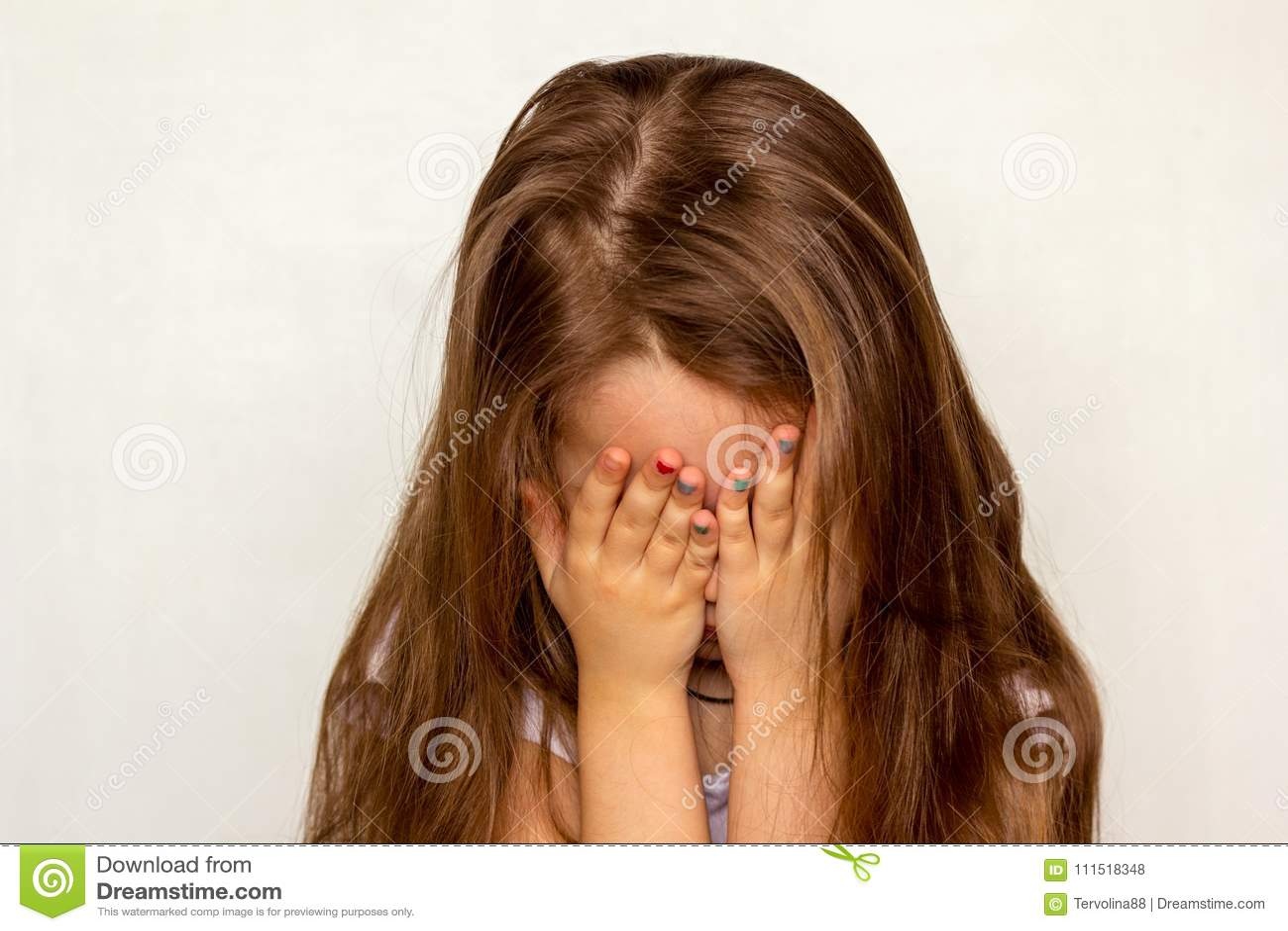 La muchacha con el pelo largo ocultó su cara con sus manos que expresaban el resentimiento