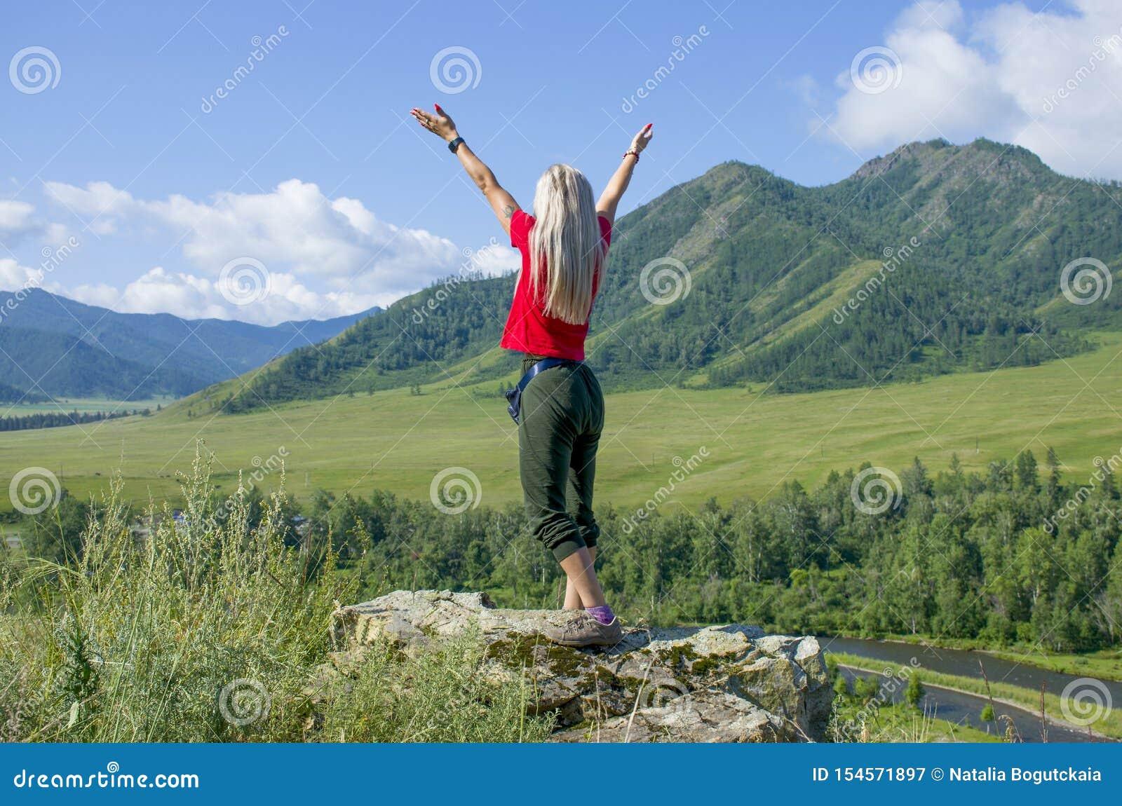 La muchacha con las manos aumentadas en las montañas Altai Rusia la visión superior