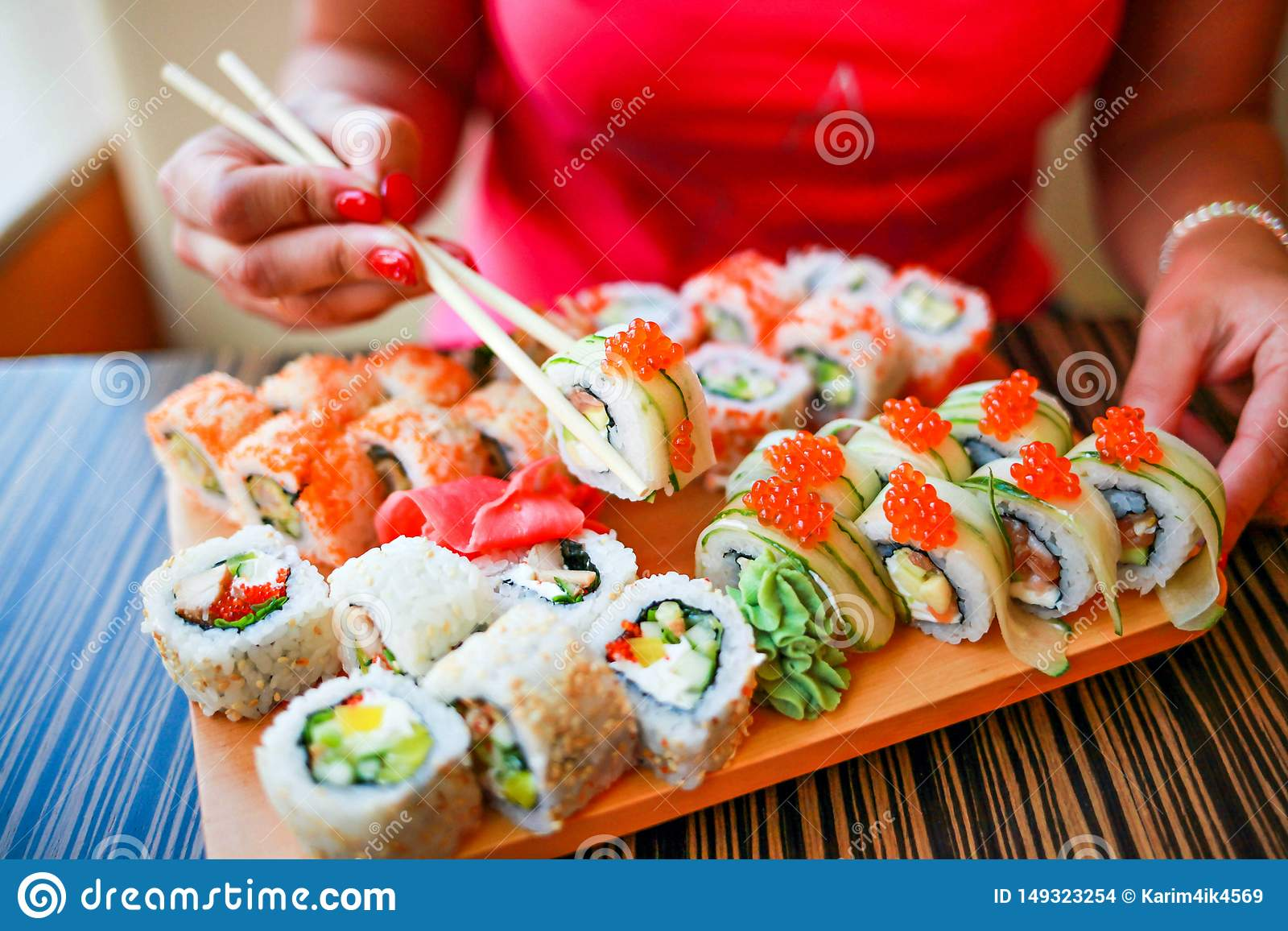 La muchacha con las manos bien arregladas sostiene los palillos para el sushi La muchacha come un sistema grande del sushi