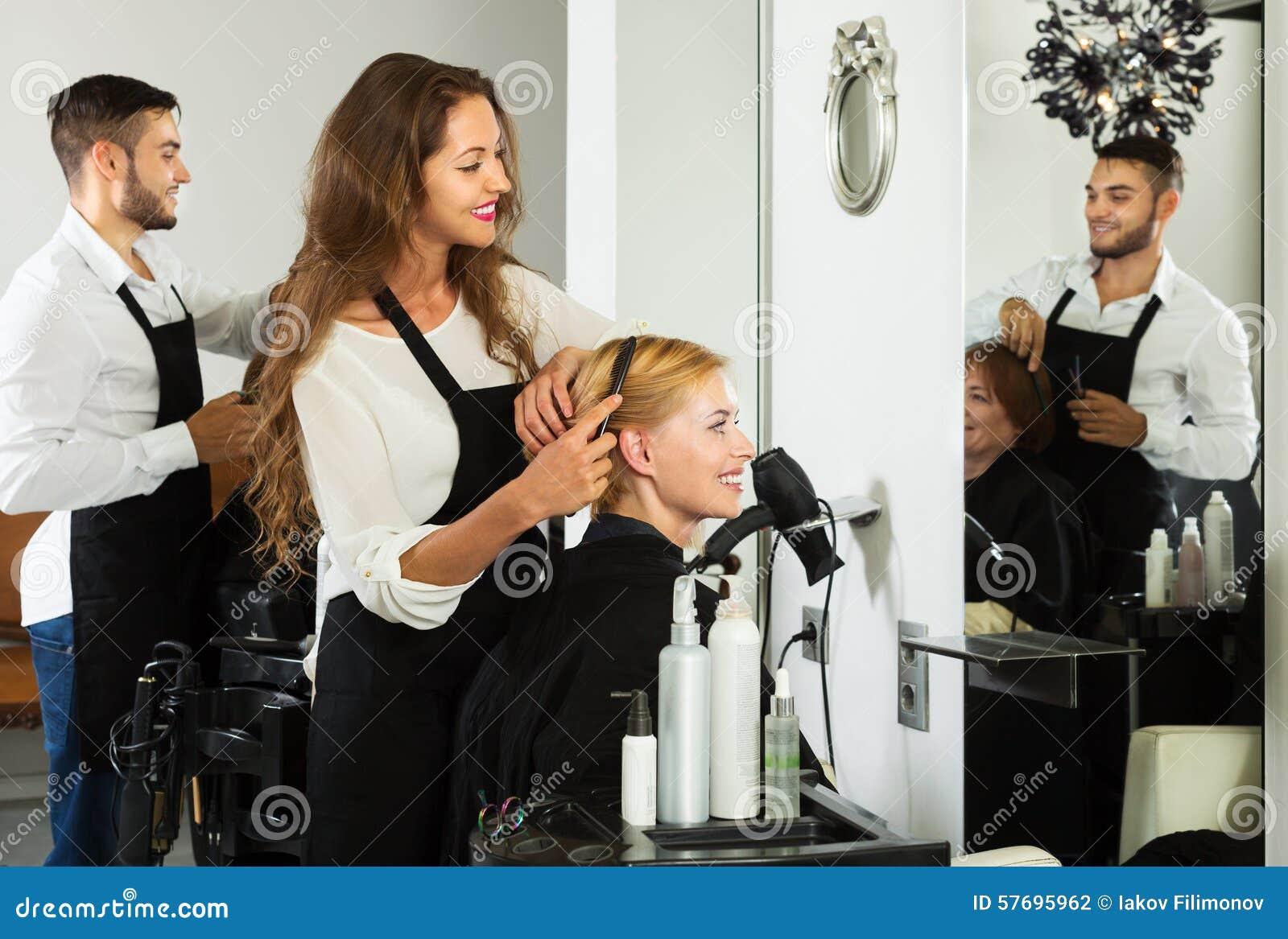 La muchacha corta el pelo en el salón de pelo