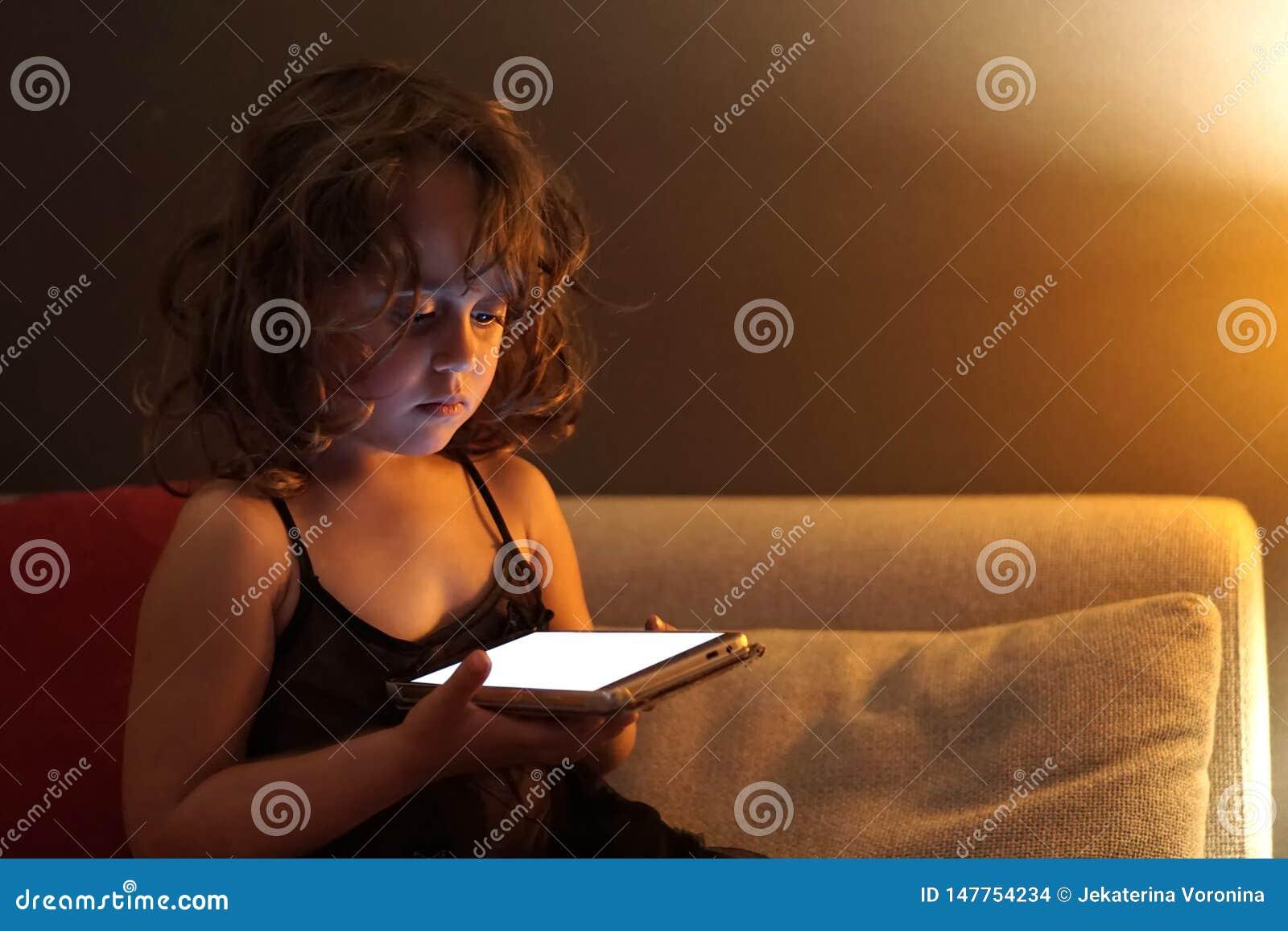 La muchacha de 3-4 a?os utiliza el tel?fono celular en la noche