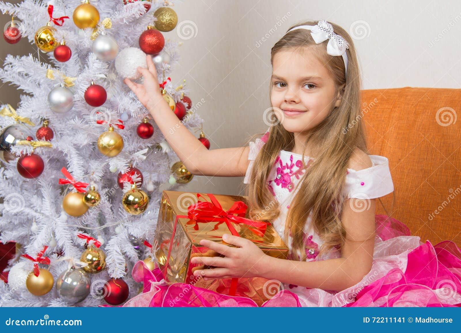 La muchacha de siete años en vestido hermoso se sienta con un regalo y sostener una bola de la Navidad en manos