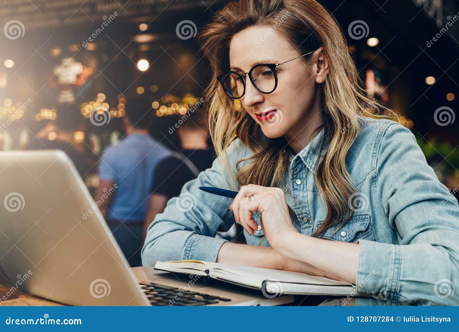 La muchacha del estudiante en vidrios de moda se sienta en café delante del ordenador, webinar educativo de los relojes del orden